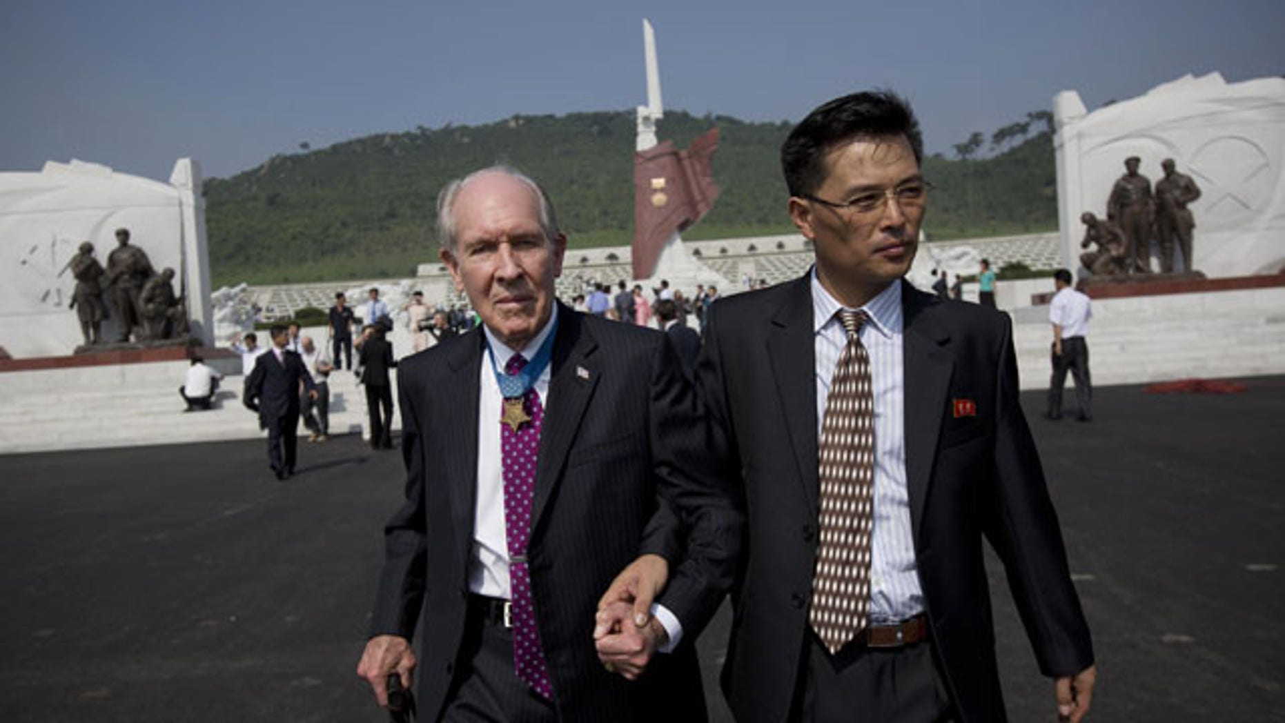 July 25, 2013: Retired U.S. Navy captain and Korean War veteran Thomas Hudner, left, is escorted by a North Korean official as he leaves a cemetery for Korean War veterans after a ceremony marking the 60th anniversary of the signing of the armistice that ended hostilities on the Korean peninsula. (AP PHOTO)