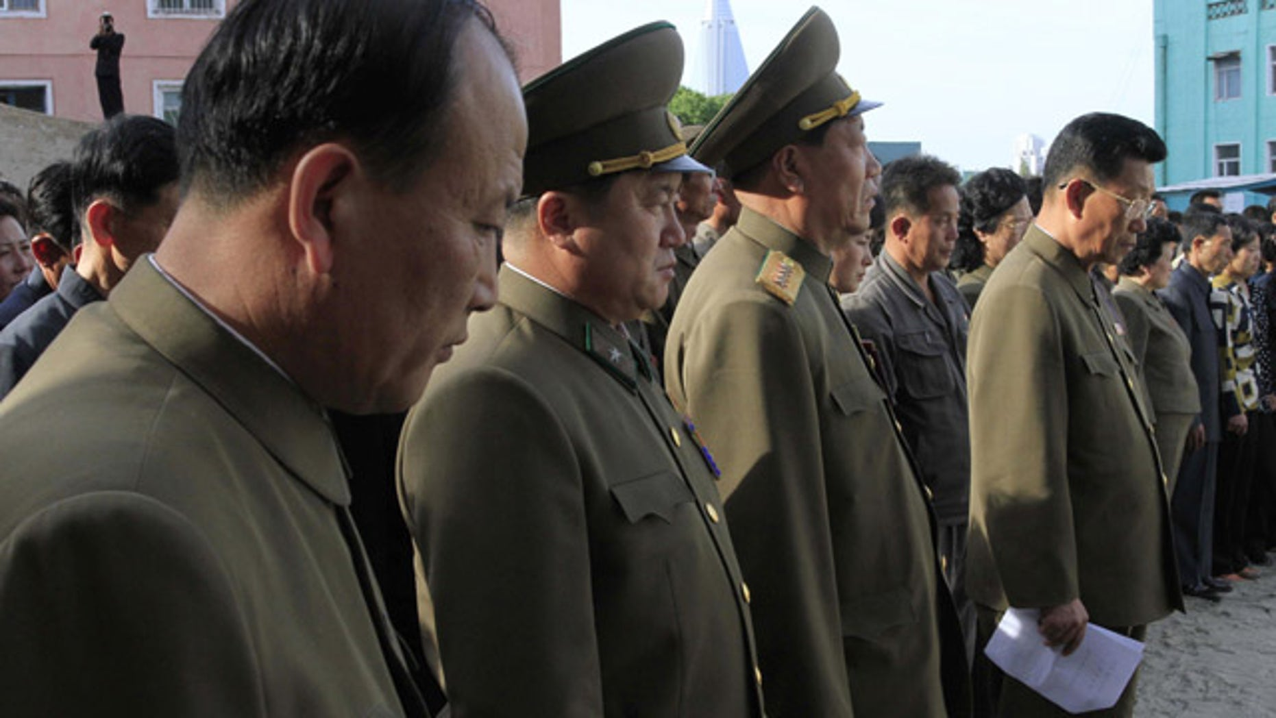 May 17, 2014: North Korean officials stand among the families of victims of an accident at an apartment construction site in Pyongyang, North Korea, during a gathering in the capital where senior officials apologized and took responsibility. (AP Photo/Kim Kwang Hyon)