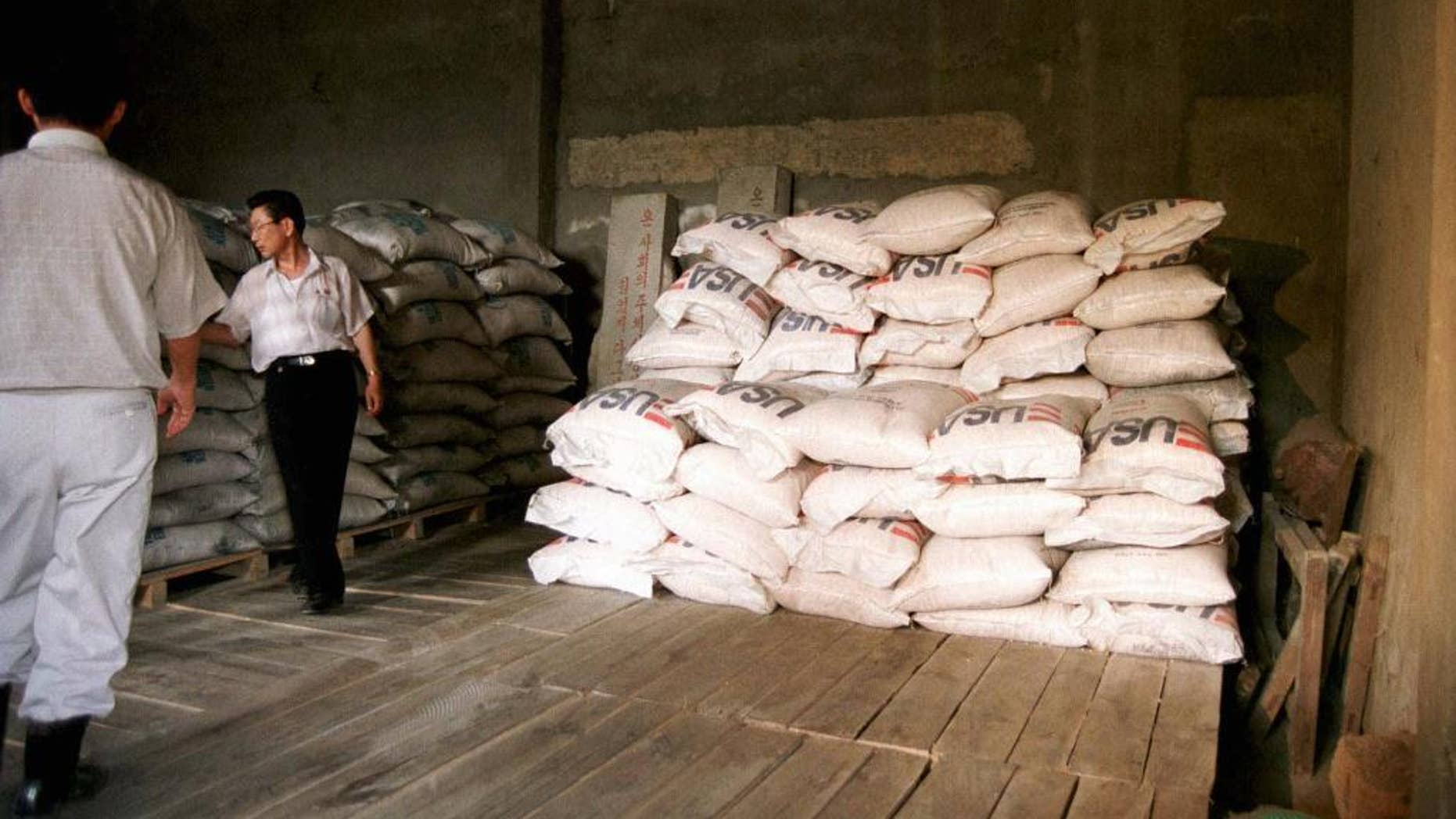 FILE - this June 26, 1997 file photo shows bags of cereal provided by the UN world food program at a corner of an almost empty warehouse used as a food storage in Hui Chon County, 200 kilometers (125 miles) northwest of Pyongyang. The U.N. agency that has provided food aid to North Korea for nearly two decades says it has enough donations to stay open for the rest of this year but is uncertain whether it will be able to operate there beyond next March. (AP Photo/UN, James Bu)
