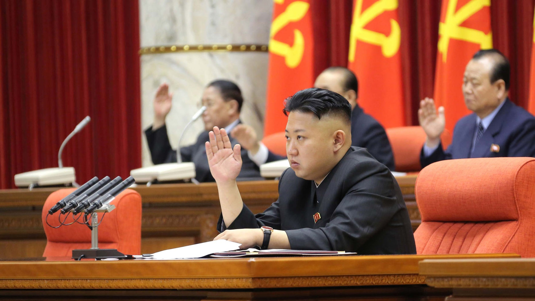 March 31, 2013: North Korean leader Kim Jong Un with other officials adopts a statement during a plenary meeting of the central committee of the ruling Workers' Party in Pyongyang, North Korea.