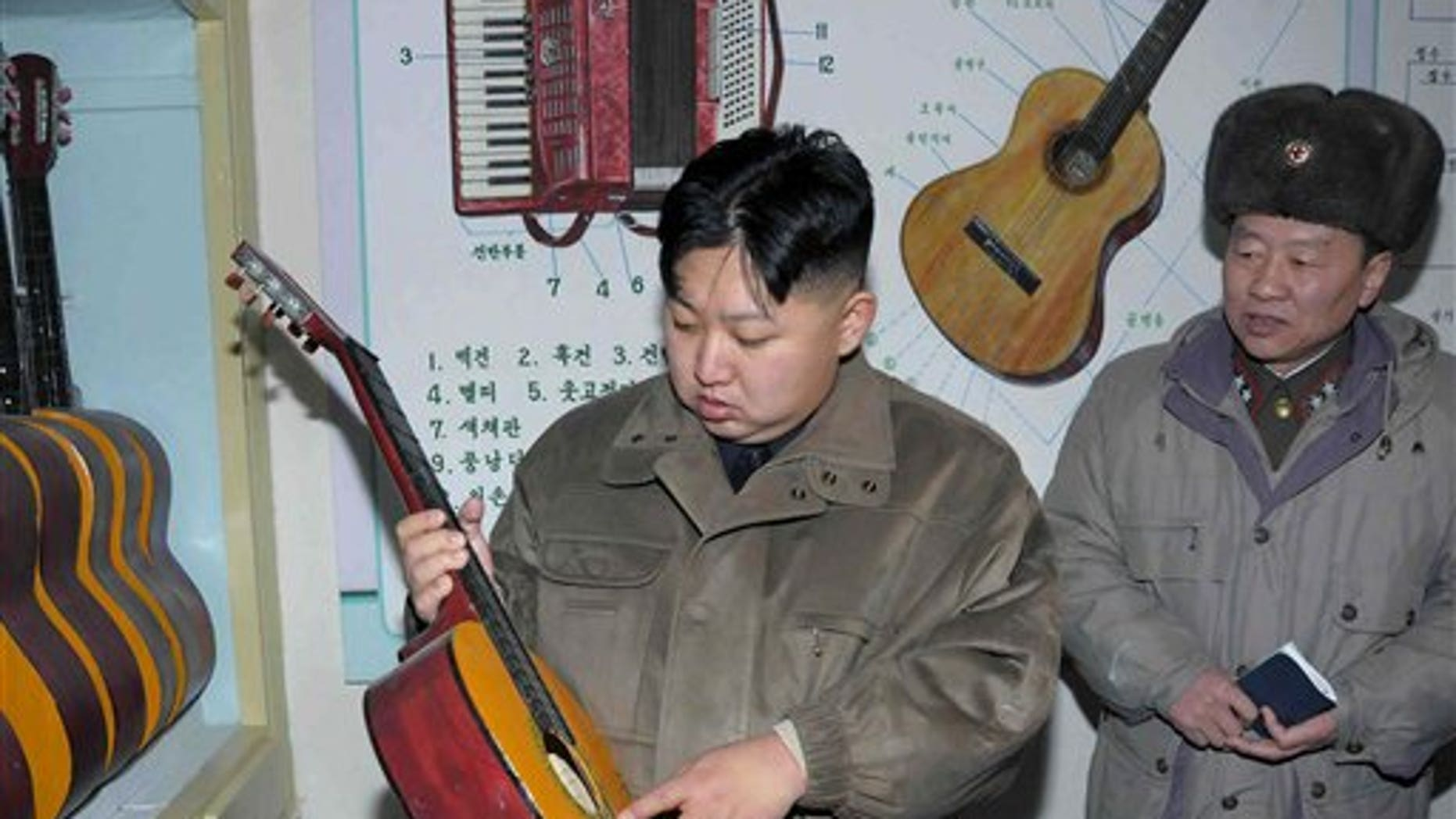 Jan. 19: In this undated photo released by the Korean Central News Agency and distributed in Tokyo by the Korea News Service, North Korean leader Kim Jong Un, center, looks at a guitar at an undisclosed location in North Korea.