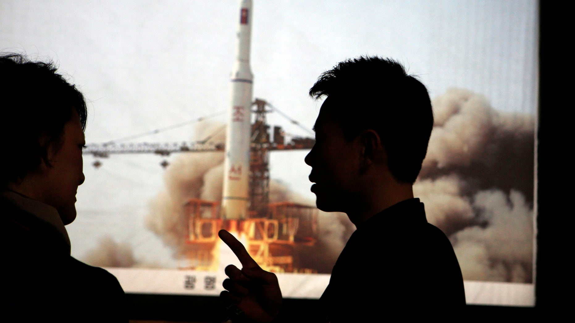 April 10, 2012: In this photo North Korean guide Kim Won Ho, right, speaks to a foreign journalist near a photo depicting the 2009 satellite rocket launch at the Three Revolutions exhibition hall in Pyongyang, North Korea.
