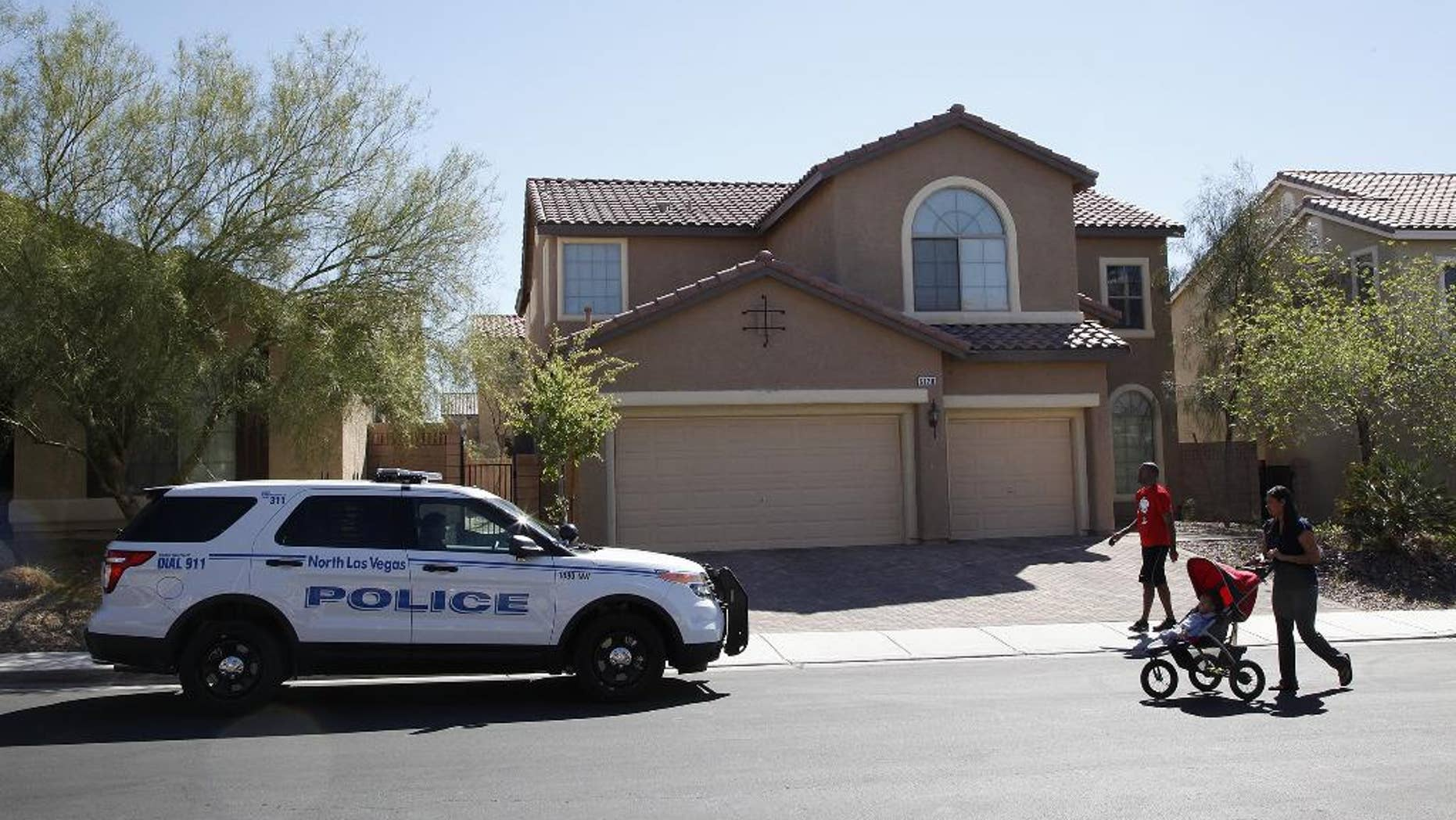 Sheldon Jacobs and his wife Nicole Jacobs walk in front of a home on the 6100 block of Stibor Street in North Las Vegas on Tuesday, April 1, 2014. Police in North Las Vegas think a family member may be responsible for a double-slaying at this home where officers sent to check on a missing 53-year-old mother and her 33-year-old daughter found a bloody crime scene. (AP Photo/Las Vegas Review-Journal, Justin Yurkanin) LOCAL TV OUT; LOCAL INTERNET OUT; LAS VEGAS SUN OUT