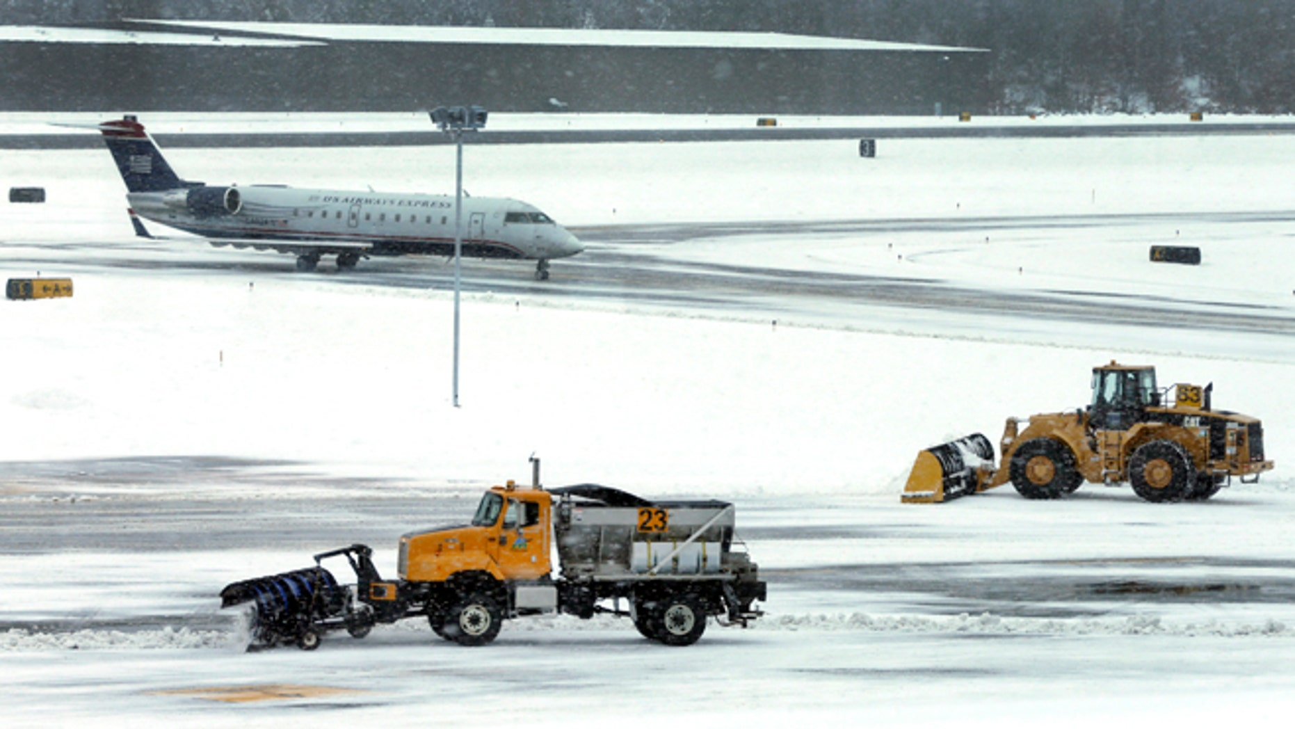 FILE - In this Thursday, Dec. 27, 2012 file photo, snow is cleared on a runway as a plane taxis into Manchester-Boston Regional Airport in Manchester, N.H.