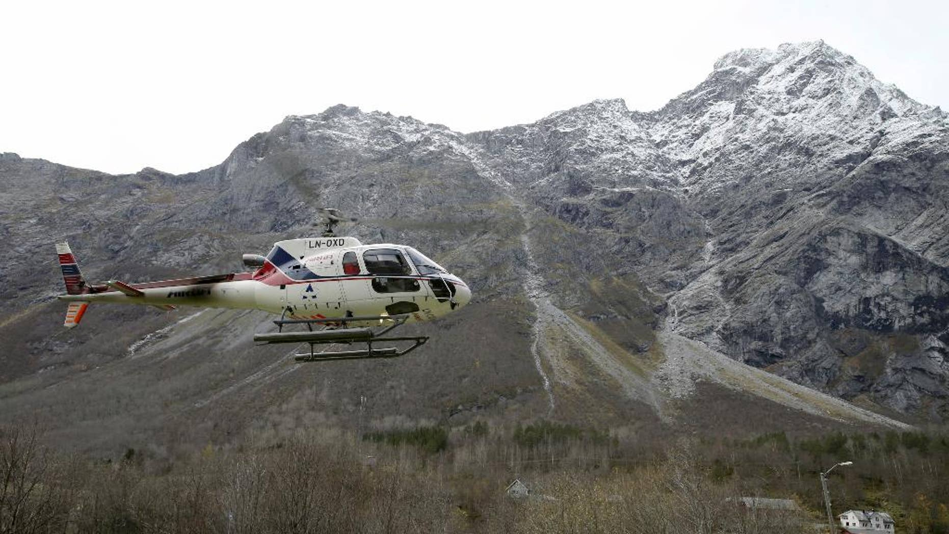 A helicopter takes off at the foot of the mountain called Mannen near Andalsnes, Norway, on Monday Oct. 27, 2014.  After being on alert for weeks experts predict a huge rockslide from the mountain within days, following heavy rain in the area. (AP Photo / Terje Pedersen, NTB scanpix) NORWAY OUT