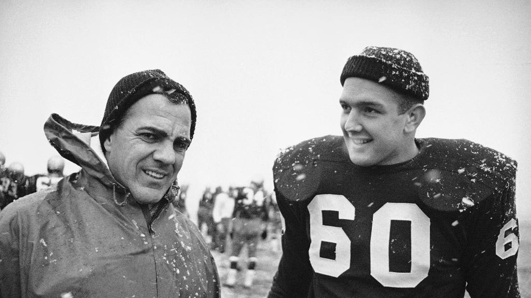 FILE - In this Nov. 20, 1964, file photo, Notre Dame coach Ara Parseghian, left, and team captain James Carroll are shown during a practice session in South Bend. Notre Dame was at rock bottom when Ara Parseghian took over 50 years ago. The Irish finished the season 2-7 in 1963 and the only thing that kept them from matching the worst record in school history set in 1956 was the game against Iowa was cancelled because of the assassination of John Kennedy.  (AP Photo/Charles Knoblock, File)