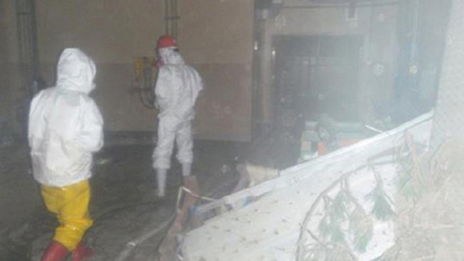 Workers wearing protective suits walk around the entrance of the crippled Fukushima Daiichi Nuclear Power Plant in Fukushima prefecture, northern Japan in this handout photo taken April 8, 2011, and released by Japan's Nuclear and Industrial Safety Agency.