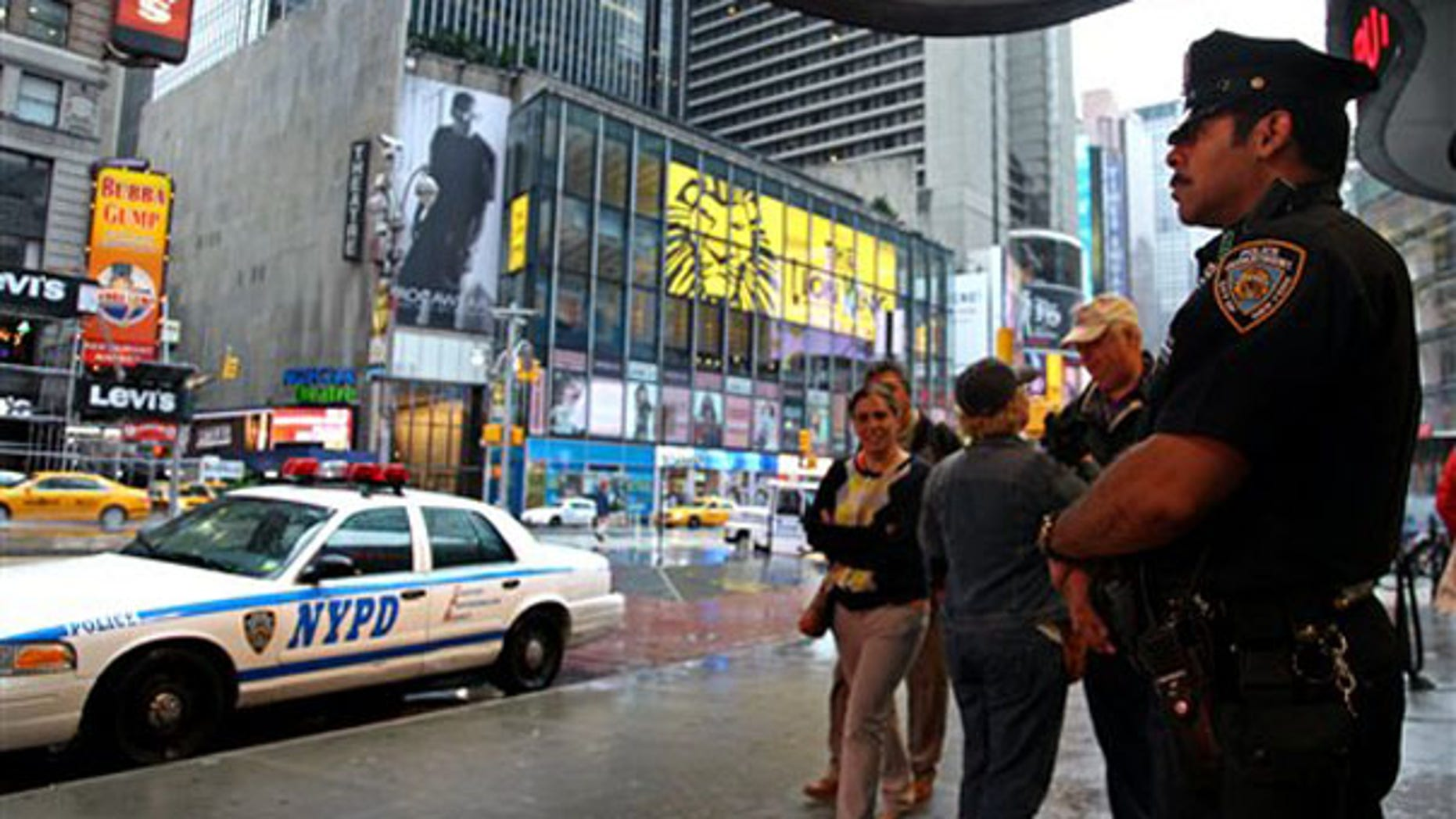 A New York City police officer stands watch in Times Square May 3 as pedestrians pass by. (AP Photo)