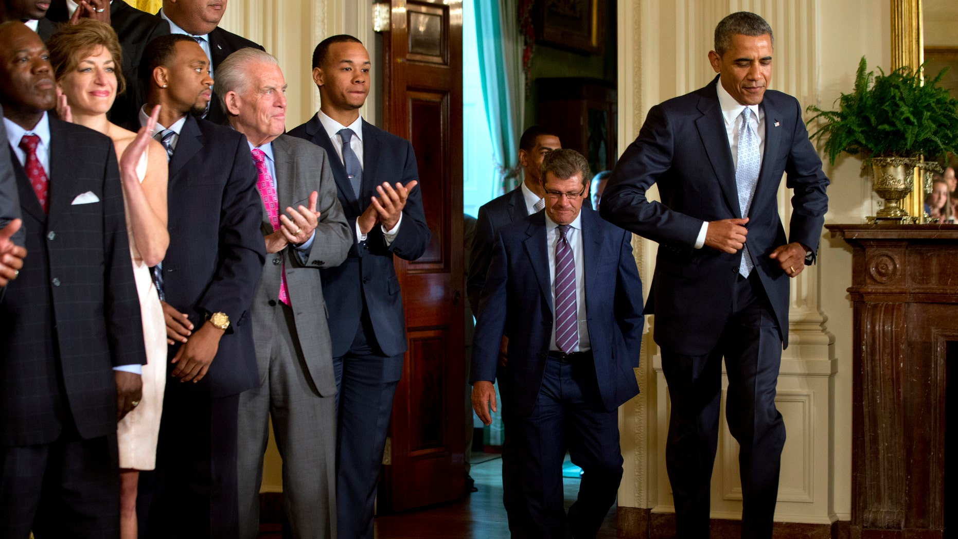 June 9, 2014: President Barack Obama jogging in to an event honoring the NCAA Basketball Champion UConn Huskies Men's and Women's Basketball teams, and their 2014 NCAA Championships in the East Room of the White House in Washington.