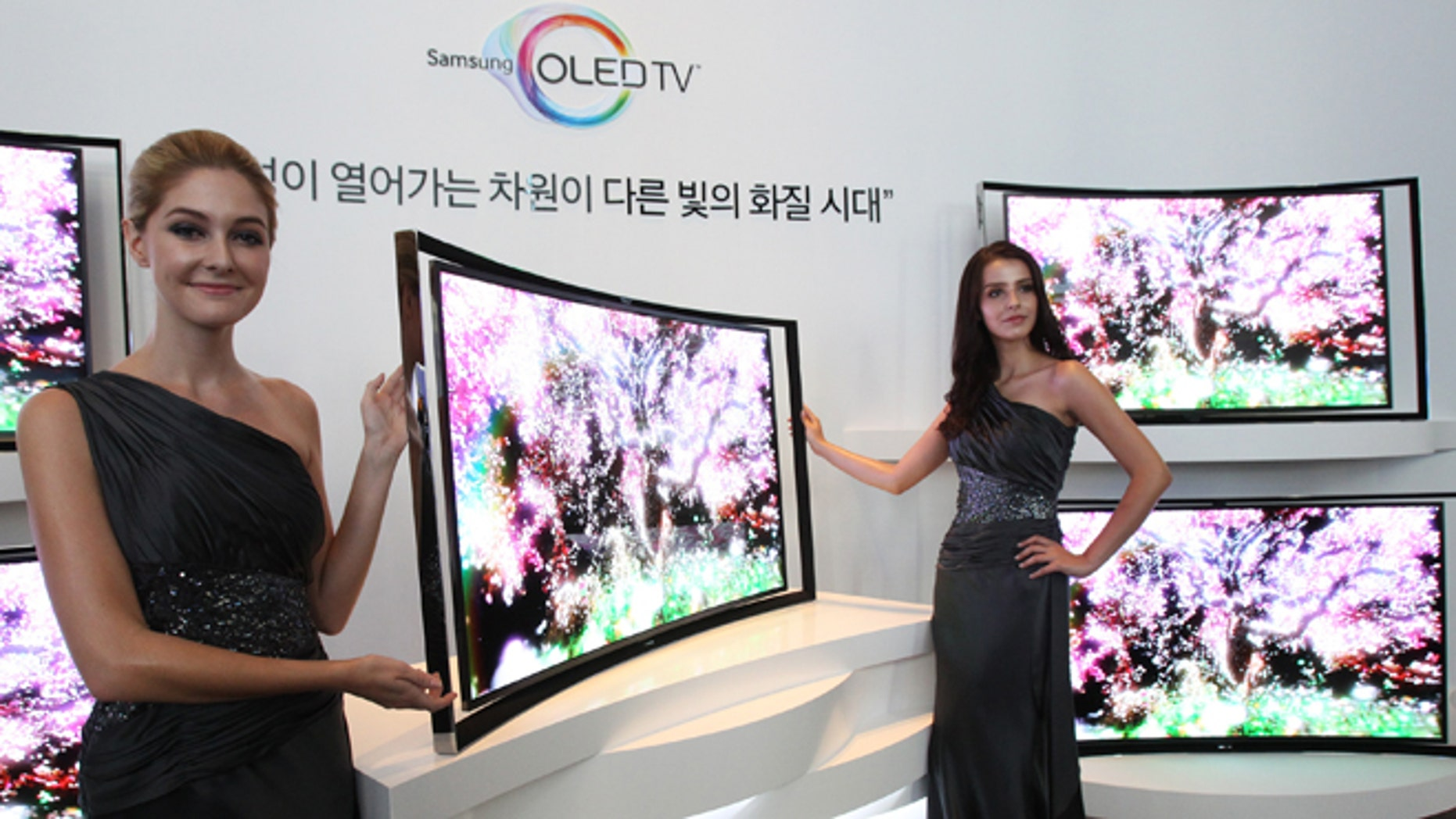 Models pose with a Samsung Electronics Co.'s 55-inch curved OLED TV during a press conference at its headquarters in Seoul, South Korea, Thursday, June 27, 2013. (AP Photo/Ahn Young-joon)