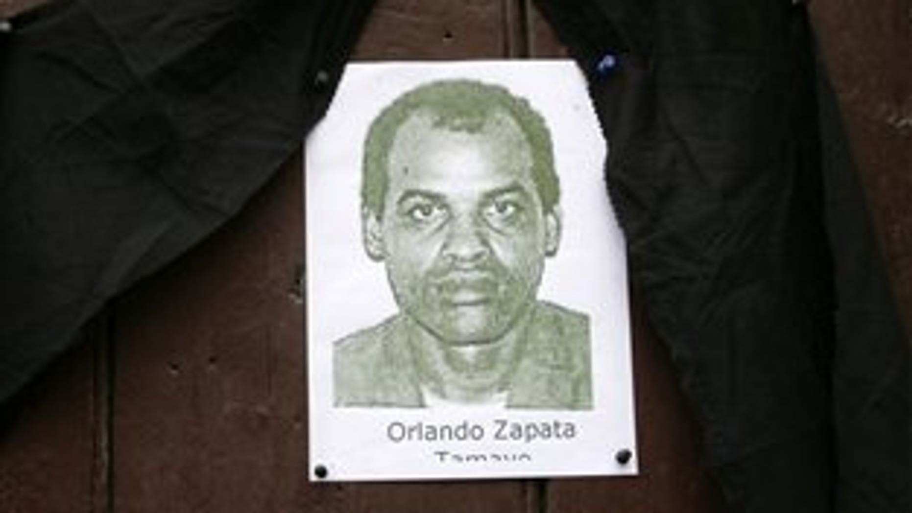 FILE - In this Feb. 24, 2010 file photo, an image of the late Cuban dissident Orlando Zapata Tamayo hangs on a door under a black ribbon in Havana, Cuba. The remains of Tamayo, who died on February 23, 2010 following an 83-day hunger strike, have been exhumed for cremation. Tamayo's mother intends to take the ashes with her on Thursday June 9, 2011 to the United States, which granted her political refuge. (AP Photo/Franklin Reyes, File)