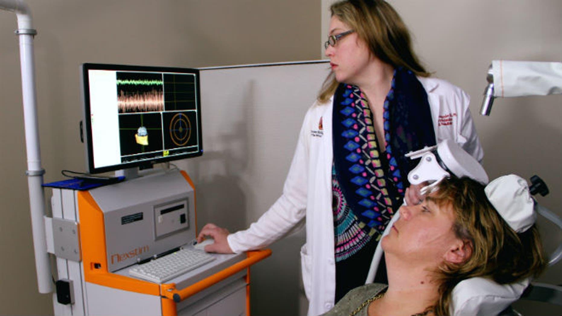 Dr. Marcie Bockbrader adjusts an external brain stimulator on stroke survivor Debbie Hall at The Ohio State University Wexner Medical Center.