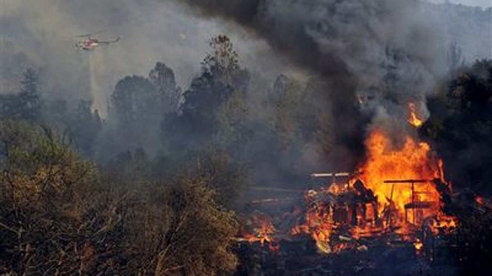 File -- August 18, 2014: A structure burns along Highway 41 in Oakhurst, Calif.  (AP Photo/The Fresno Bee, Eric Paul Zamora)
