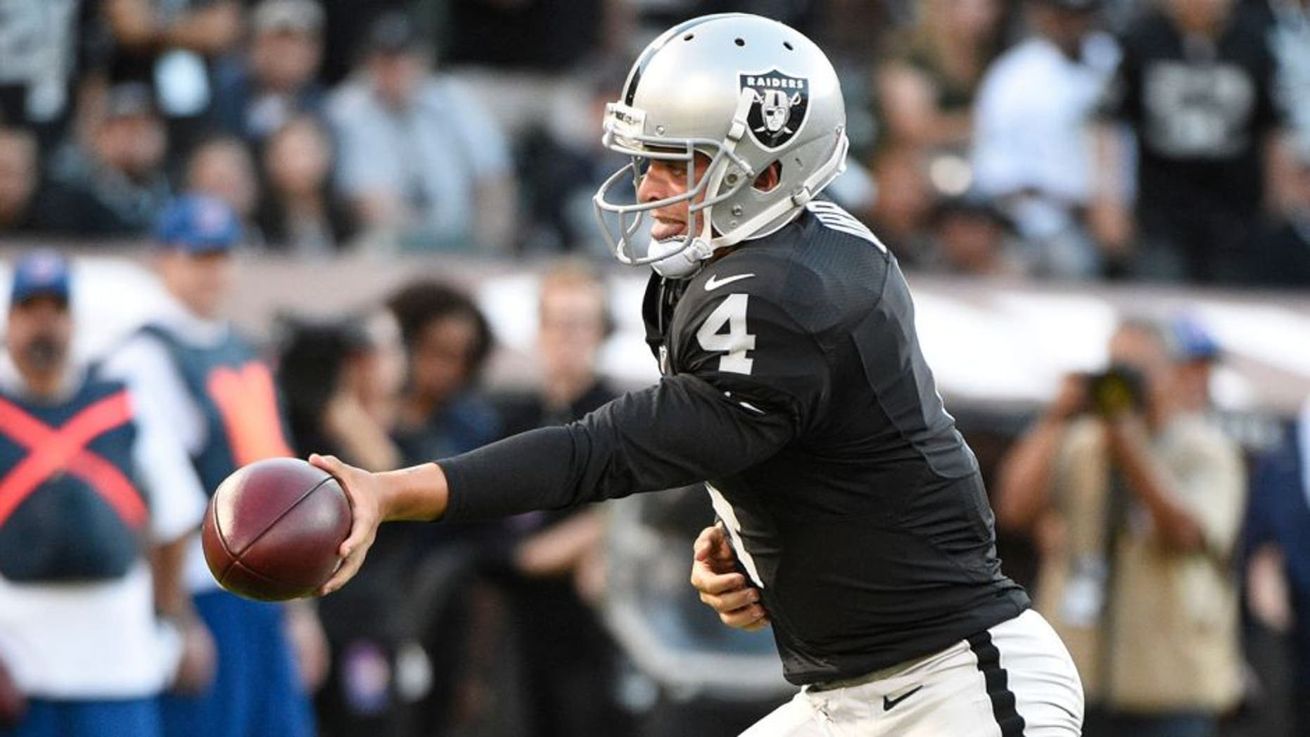 August 14, 2015; Oakland, CA, USA; Oakland Raiders quarterback Derek Carr (4) hands the football off against the St. Louis Rams during the first quarter in a preseason NFL football game at O.co Coliseum. Mandatory Credit: Kyle Terada-USA TODAY Sports