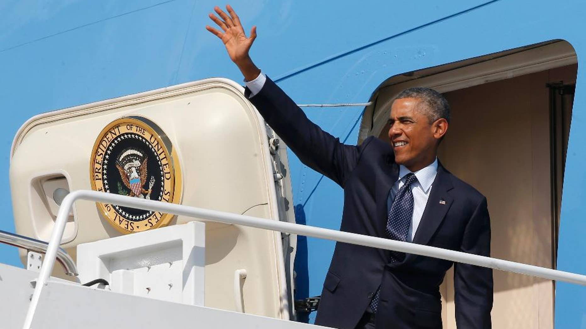 President Barack Obama waves as he boards Air Force One at Andrews Air Force Base, Md., Tuesday, Sept. 2, 2014, as he begins his trip to Estonia and Wales for the NATO Summit. (AP Photo/Charles Dharapak)