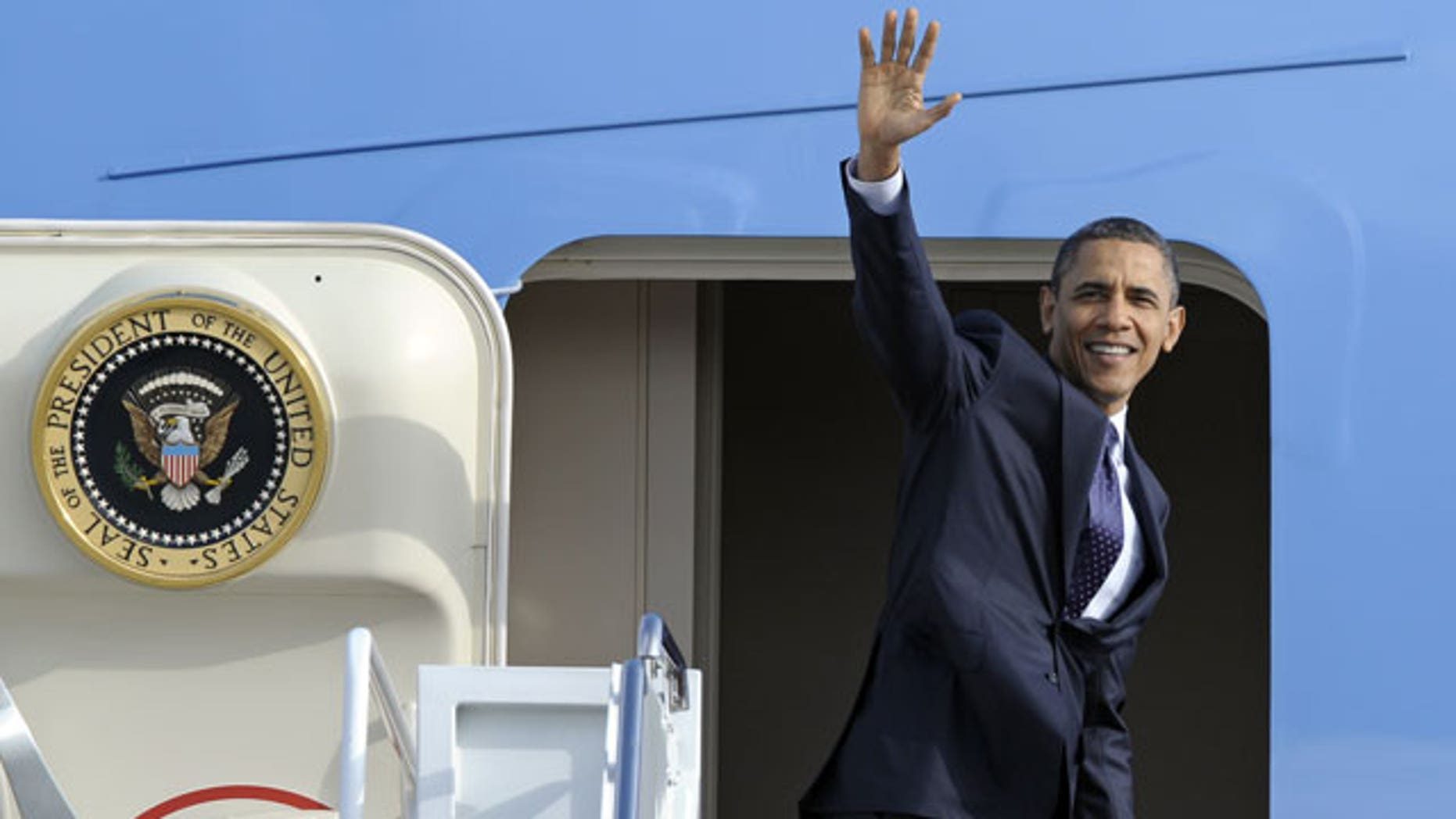 December 23, 2011: President Barack Obama waves as he boards Air Force One at Andrews Air Force Base, Md.