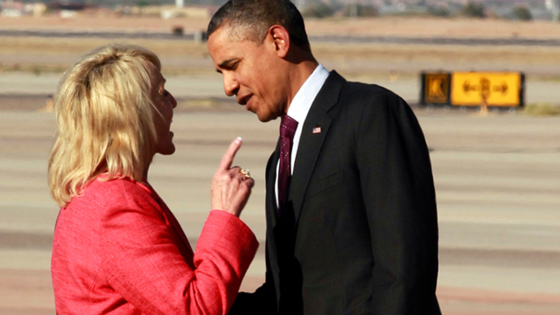 Jan. 25, 2012: Arizona Gov. Jan Brewer points at President Obama after he arrived at Phoenix-Mesa Gateway Airport.