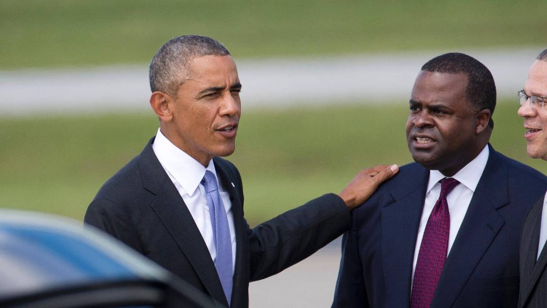 President Barack Obama chats with Atlanta Mayor Kasim Reed after  arriving at Hartsfield Jackson Atlanta International Airport in Atlanta for a scheduled visit to the Centers for Disease Control and Prevention  for a briefing on West Africa's Ebola out break, Tuesday, Sept. 16, 2014. (AP Photo/John Bazemore)