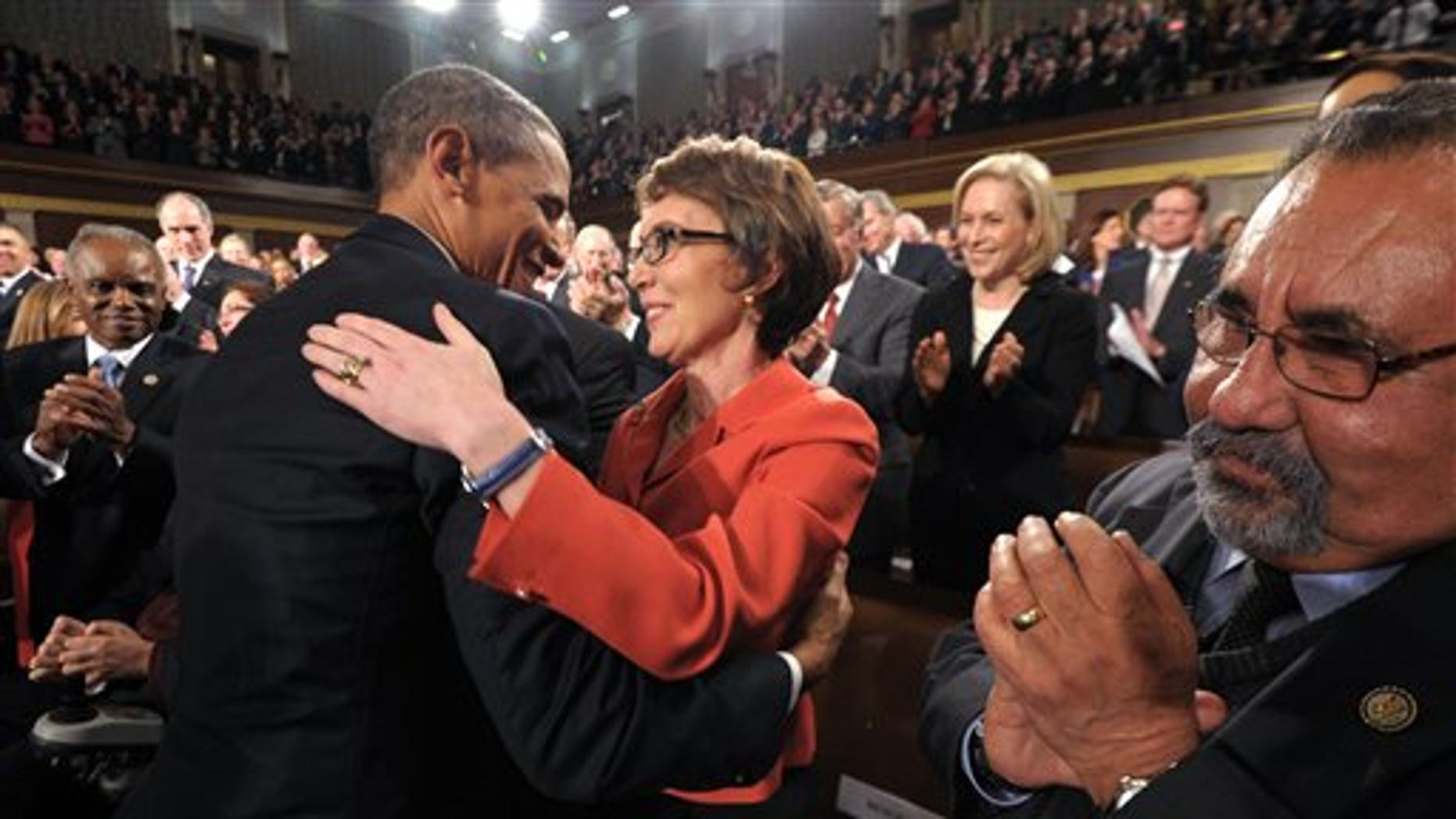 Jan. 24, 2012: President Obama embraces retiring Rep. Gabrielle Giffords, D-Ariz., as members of Congress applaud before his State of the Union address.