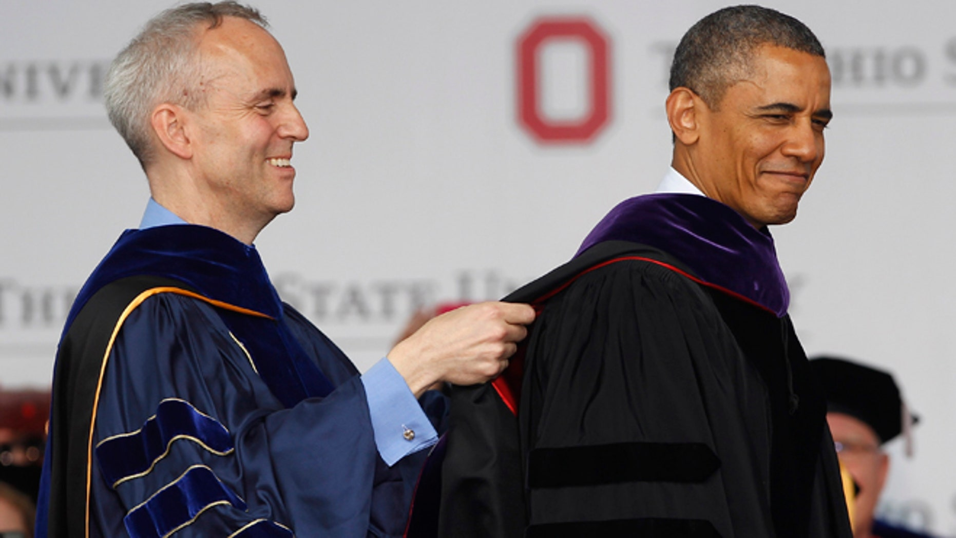 COLUMBUS, OH - MAY 05:  Ohio State Trustee David Horn (L) puts a sash on U.S. President Barack Obama during commencement ceremonies at The Ohio State University at Ohio Stadium on May 5, 2013 in Columbus, Ohio. Obama addressed the graduates a year from the day he kicked off his re-election campaign at the campus.The president was also given an honorary degree Doctor of Laws. (Photo by Matt Sullivan/Getty Images)
