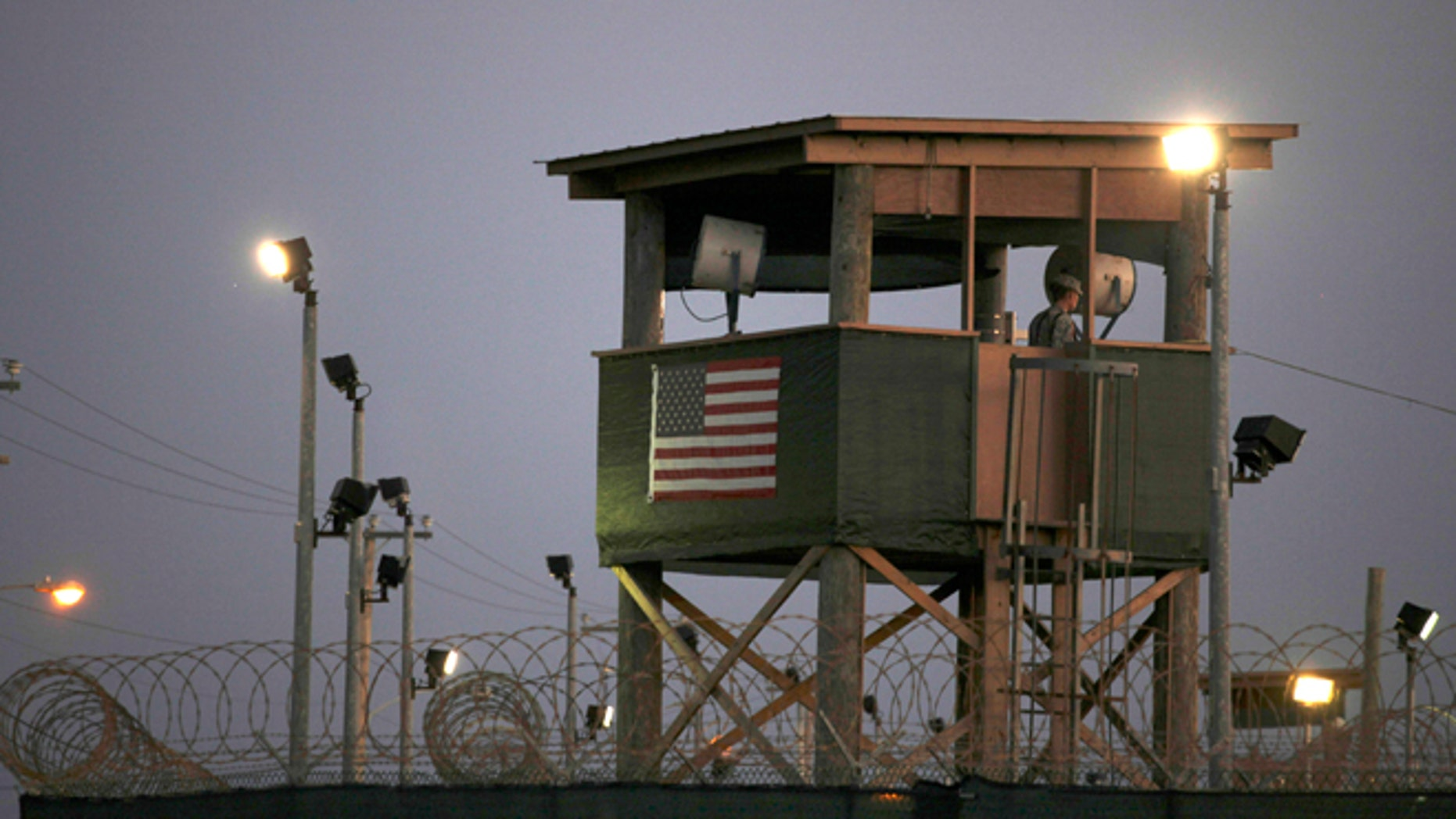 FILE - In this March 29, 2010 photo, reviewed by the U.S. military, a Guantanamo guard keeps watch from a tower overlooking the detention facility at Guantanamo Bay U.S. Naval Base, Cuba. The transfer of prisoners out of Guantanamo Bay has ground to a halt amid a slow Pentagon approval process. Thatâs caused frustration within the administration and raised doubts that President Barack Obama can fulfill his campaign promise to close the U.S. prison Cuba for terrorism suspects. (AP Photo/Brennan Linsley, File)