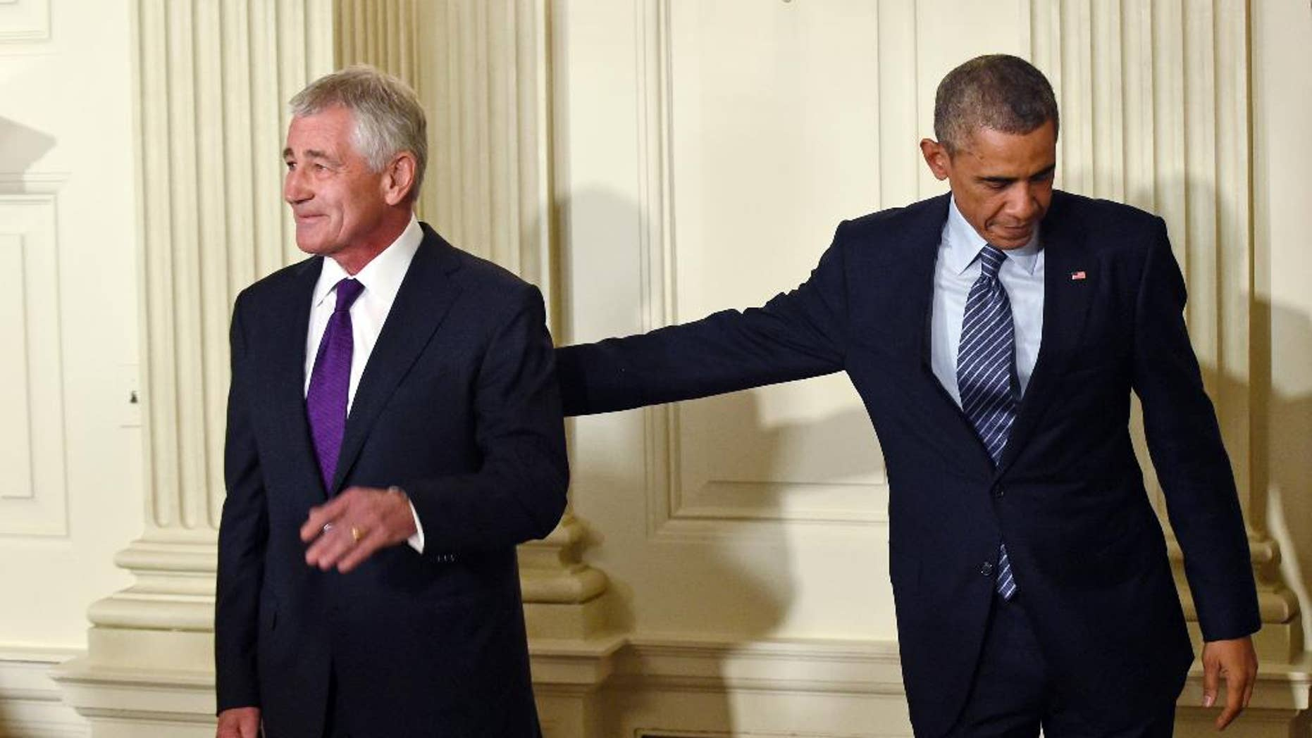 President Barack Obama, left, reaches over to touch Defense Secretary Chuck Hagel, left, following an announcement of Hagel's resignation during an event in the State Dining Room of the White House in Washington, Monday, Nov. 24, 2014. Hagel is stepping down under pressure from Obama's Cabinet, senior administration officials said Monday, following a tenure in which he has struggled to break through the White House's insular foreign policy team. (AP Photo/Susan Walsh)