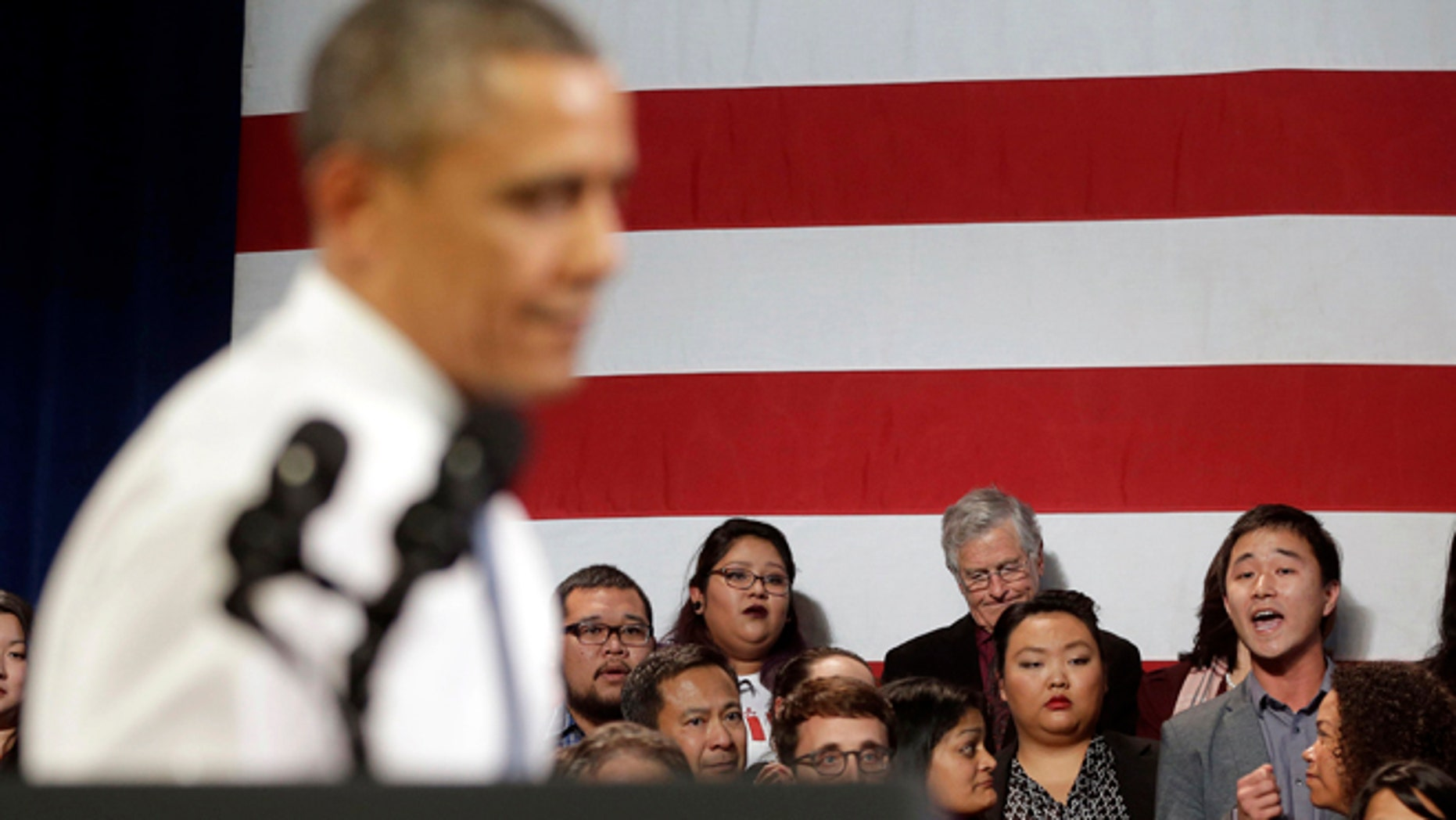 In this Nov. 25, 2013, photo, President Barack Obama, left, stops his speech and turns around in response to an unidentified man, right, who heckled him about anti-deportation policies, at the Betty Ann Ong Chinese Recreation Center in San Francisco. Obama stopped his speech about immigration reform to let this man, who was located directly behind Obama, speak and would respond to his questions. Advocates are frustrated with the failure of House Republicans to tackle immigration. Increasingly, theyâre focus is on President Barack Obama. The outside groups are demanding that Obama use his powers as chief executive to stop deportations or provide some relief to many of the 11 million immigrants living here illegally.  (AP Photo/Pablo Martinez Monsivais, File)