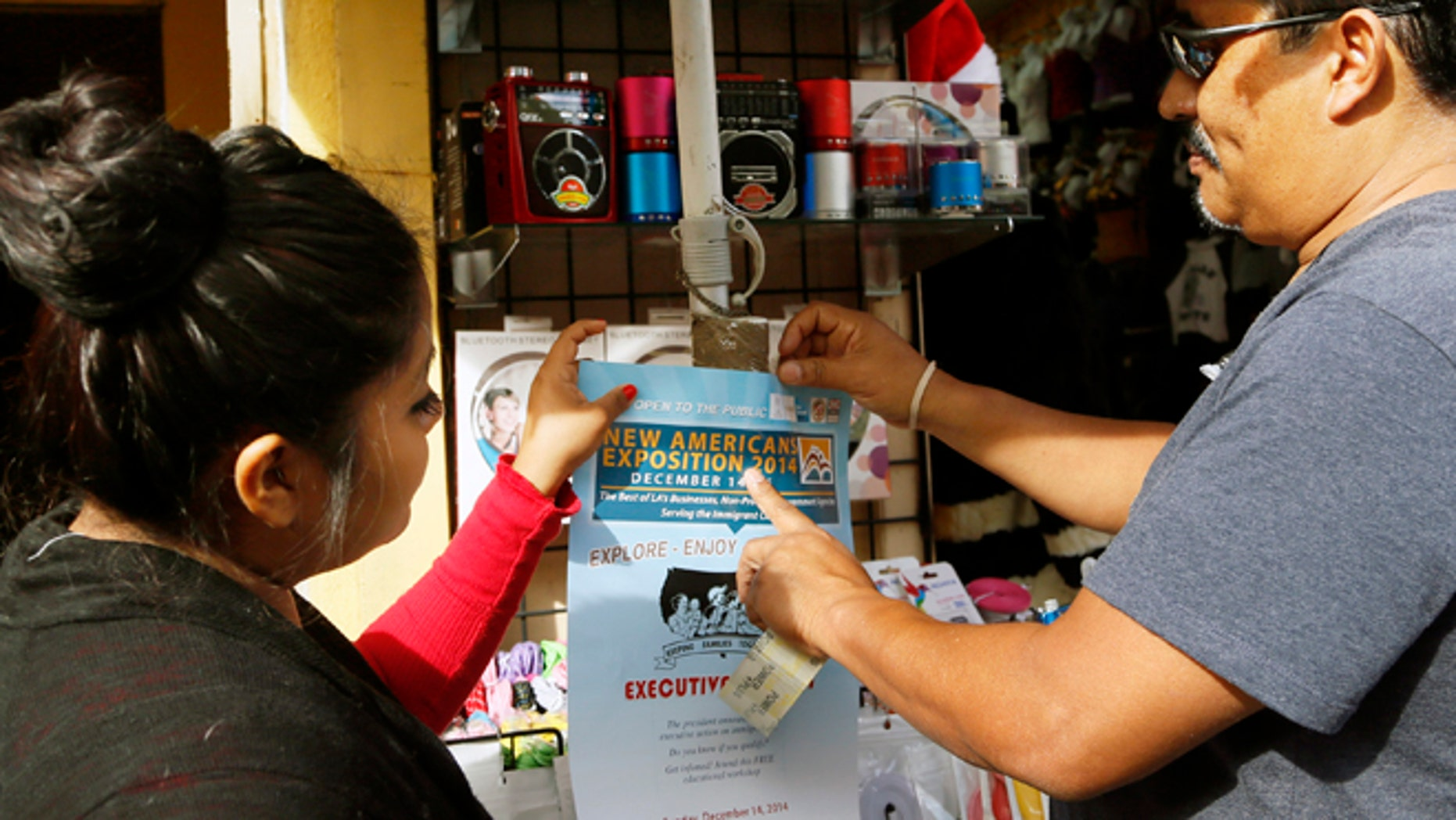 This Dec. 10, 2014 photo shows Lucero Vega watches as Tony Bernabe, right, posts a flier in downtown Los Angeles advertising a massive information session scheduled for this weekend to tell immigrants more about President Barack Obamas executive actions on immigration. Immigrant advocates have been holding workshops in churches, schools and meeting rooms across the country to dispel rumors, ward off fraud and help immigrants here illegally determine if they qualify to apply for a work permit and protection from deportation.   (AP Photo/Nick Ut)