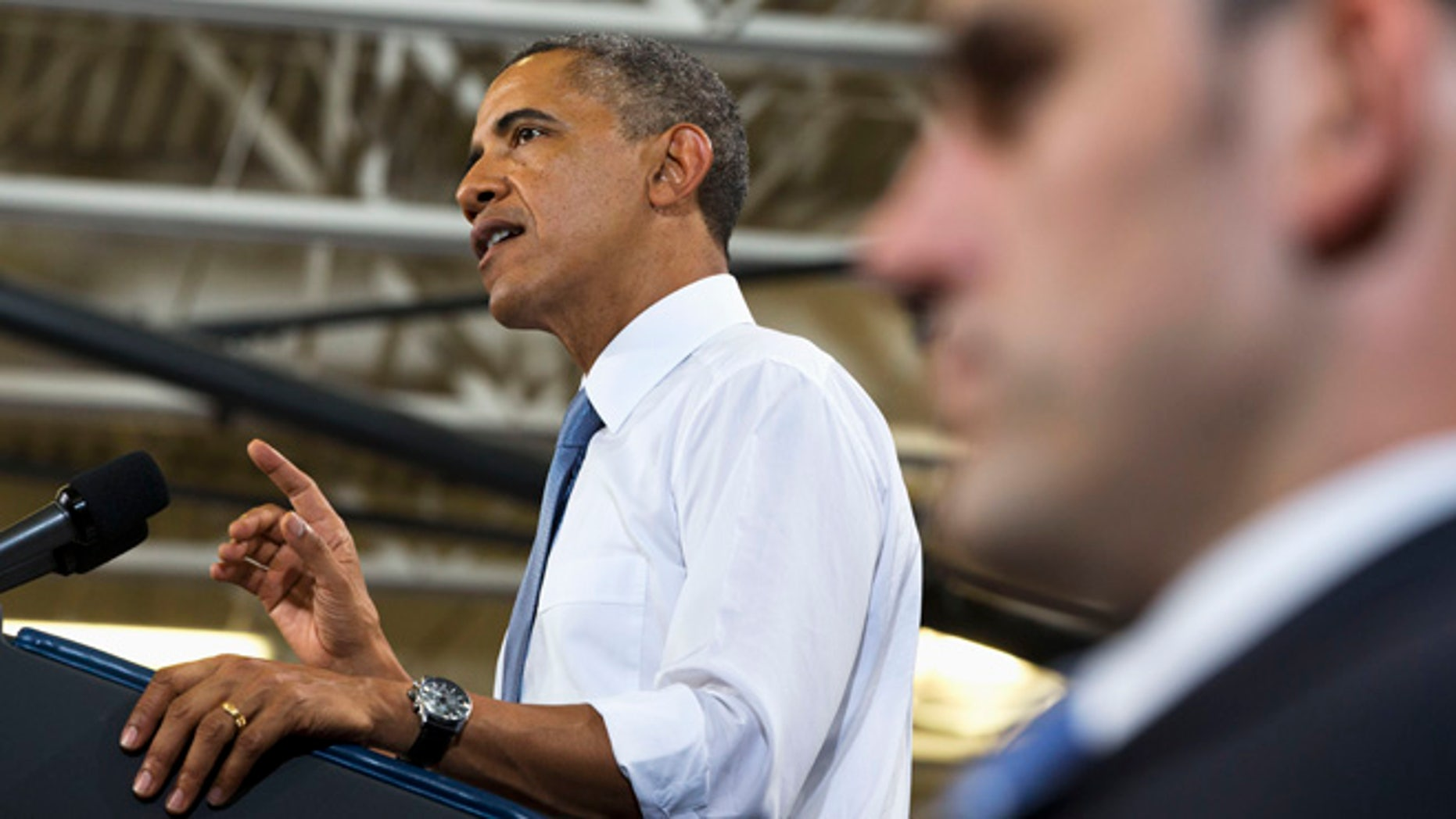 With a Secret Service agent in the foreground, President Obama gestures as he speaks about housing, Tuesday, Aug. 6, 2013, at Desert Vista High School in Phoenix.