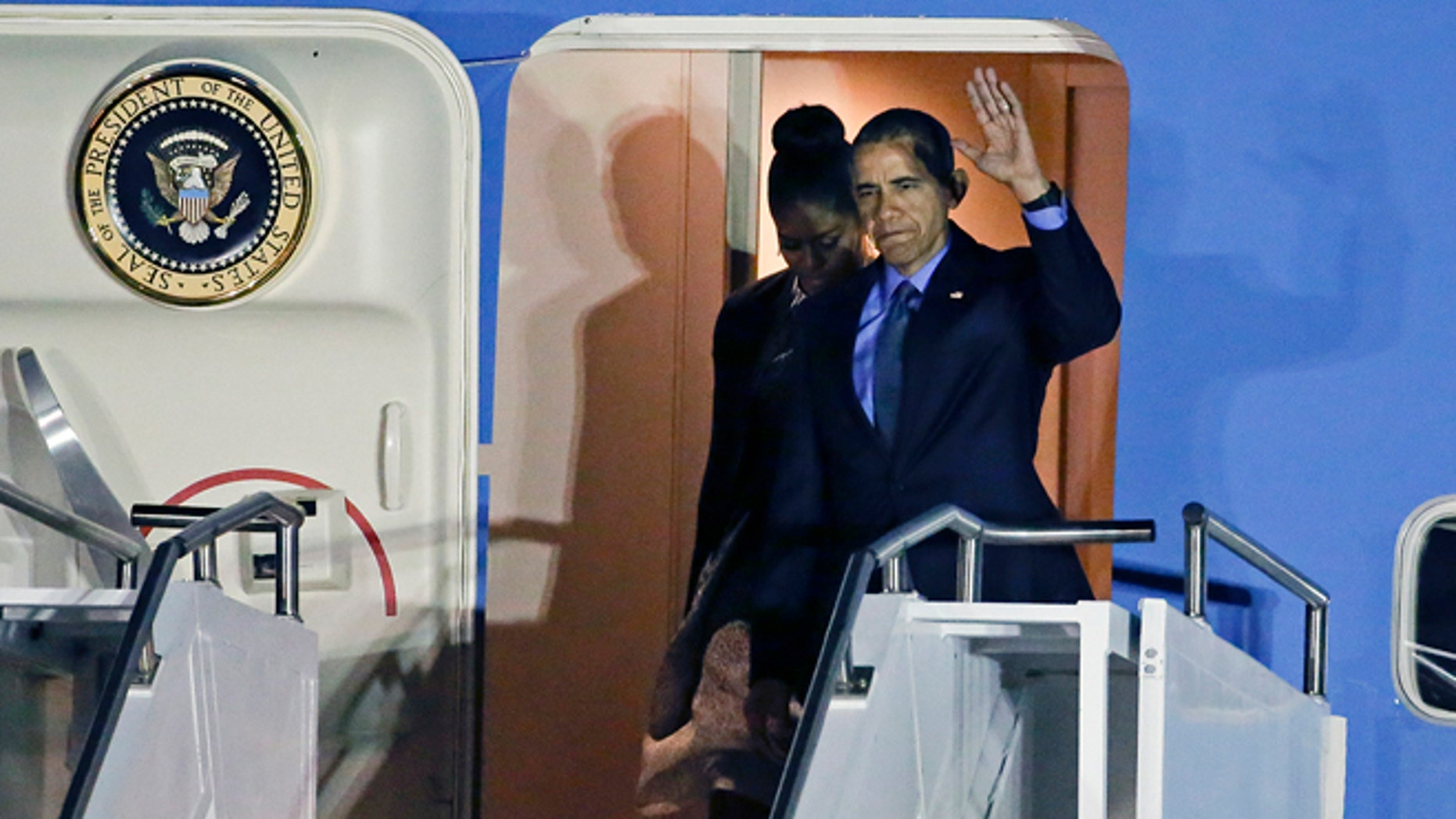 President Barack Obama, right, and first lady Michelle Obama, arrive at San Bernardino International Airport, on Friday, Dec. 18, 2015, in San Bernardino, Calif. Obama is meeting with families of the victims of a mass shooting that struck the community. (AP Photo/Chris Carlson)