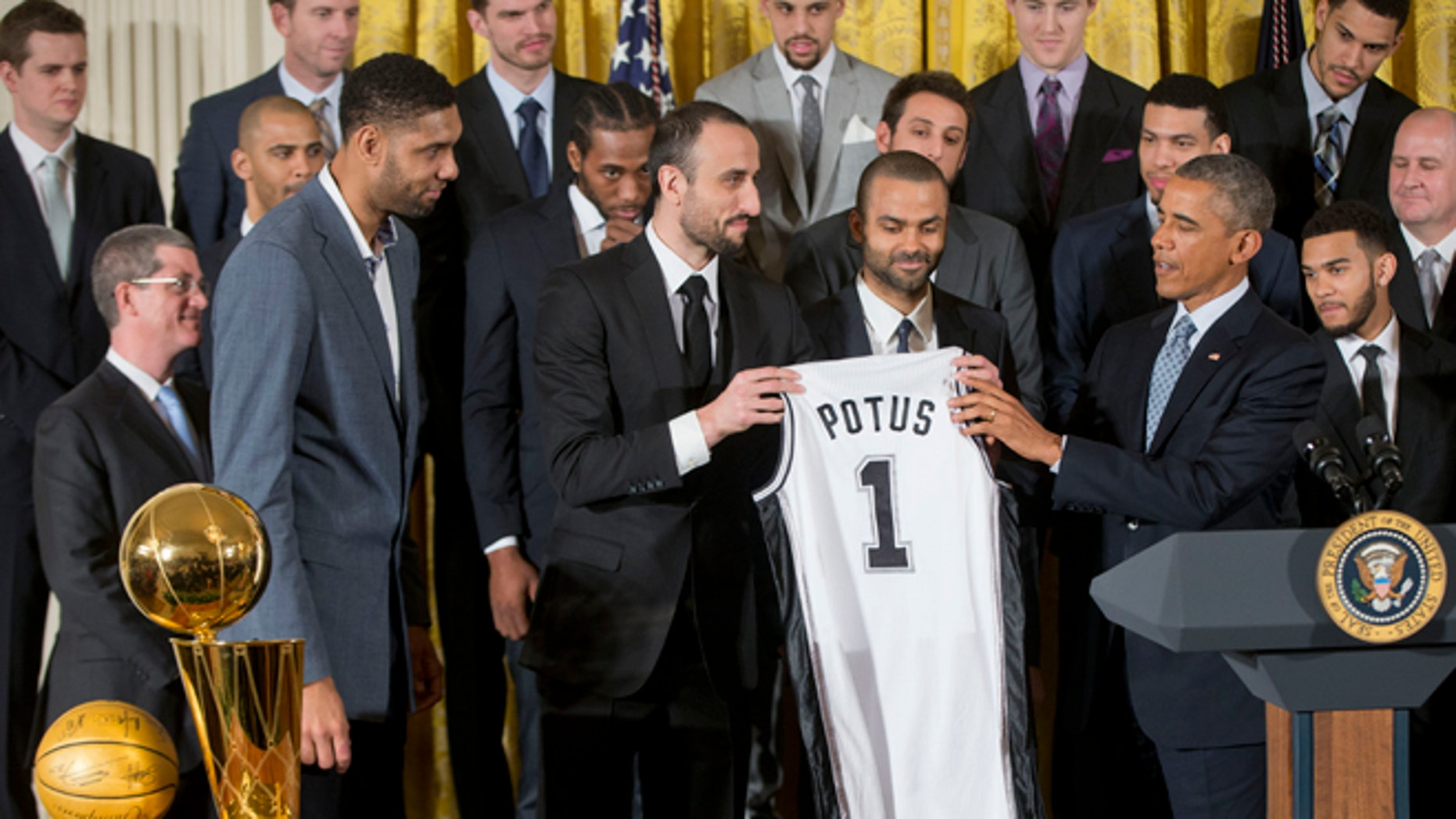 President Barack Obama accepts a San Antonio Spurs team basketball jersey from San Antonio Spurs team members, from left, forward Tim Duncan of the Virgin Islands, guard Manu Ginobili of Argentina, and guard Tony Parker of France, as the president honored the 2014 NBA Champions the San Antonio Spurs basketball team during a ceremony in the East Room White House in Washington, Monday, Jan. 12, 2015.  (AP Photo/Pablo Martinez Monsivais)