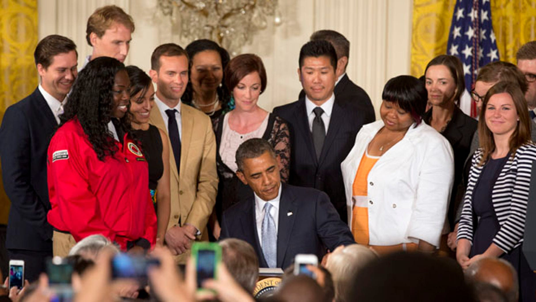 Surrounded by college students, President Barack Obama signs a Presidential Memorandum on reducing the burden of student loan debt, Monday, June 9, 2014, in the East Room of the White House in Washington.