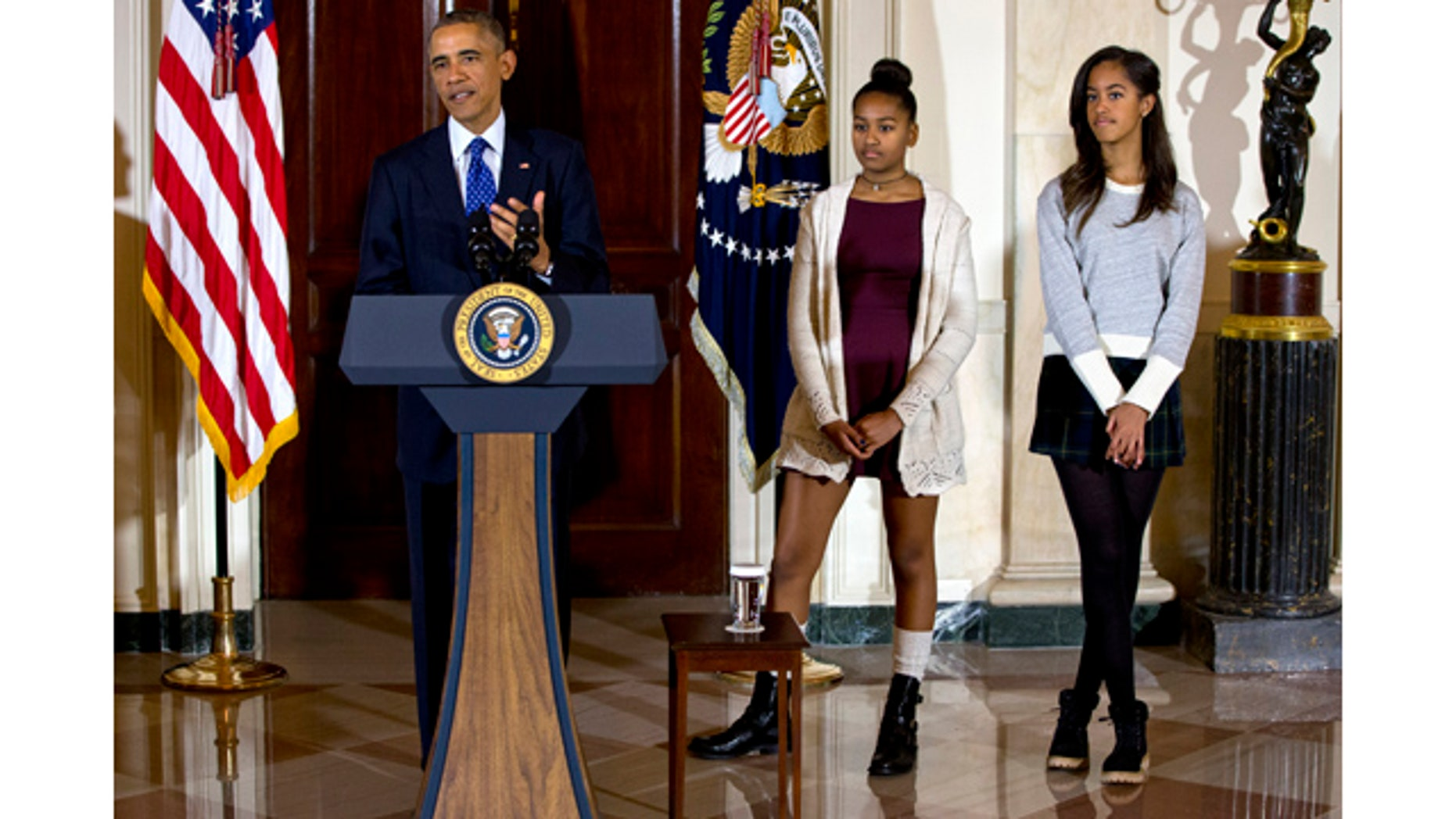November 26, 2014: President Barack Obama, joined by his daughters Malia, right, and Sasha, center, speaks during the presidential turkey pardon ceremony at the White House. (AP Photo/Jacquelyn Martin)