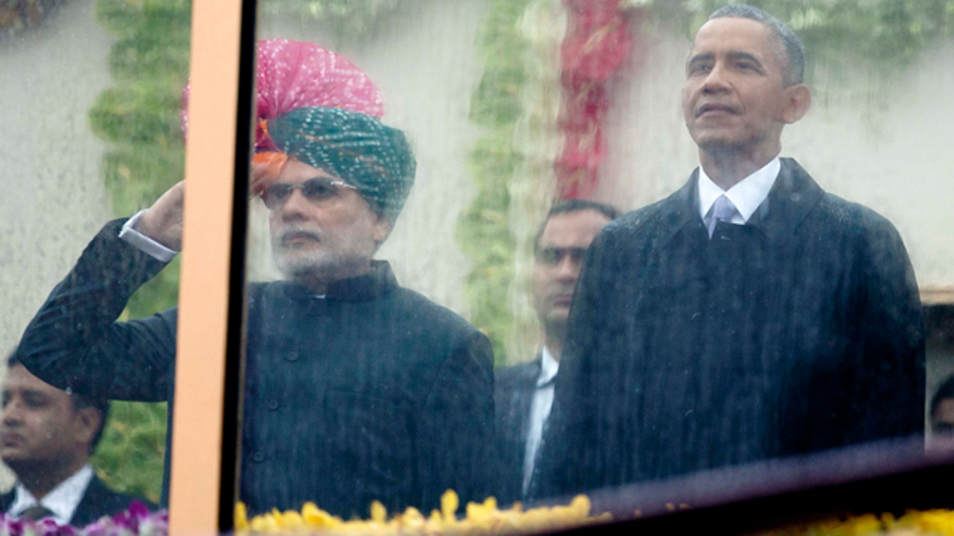 Jan. 26, 2015: Indian Prime Minister Narendra Modi, left, and U.S. President Barack Obama, right, look out through rain covered protective glass to watch the Republic Day Parade in New Delhi. (AP Photo/Carolyn Kaster)