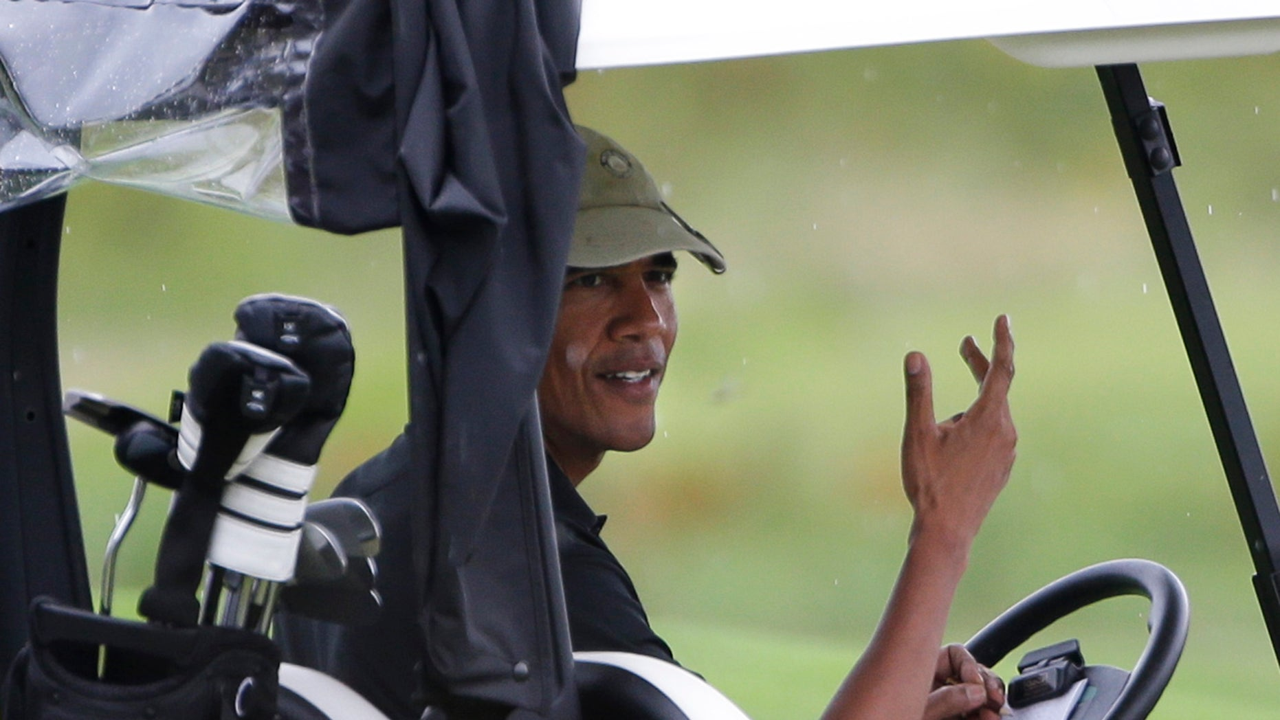 President Barack Obama gestures from his golf cart off while golfing at Vineyard Golf Club in Edgartown, Mass., on the island of Martha's Vineyard Sunday, Aug. 18, 2013. (AP Photo/Steven Senne)