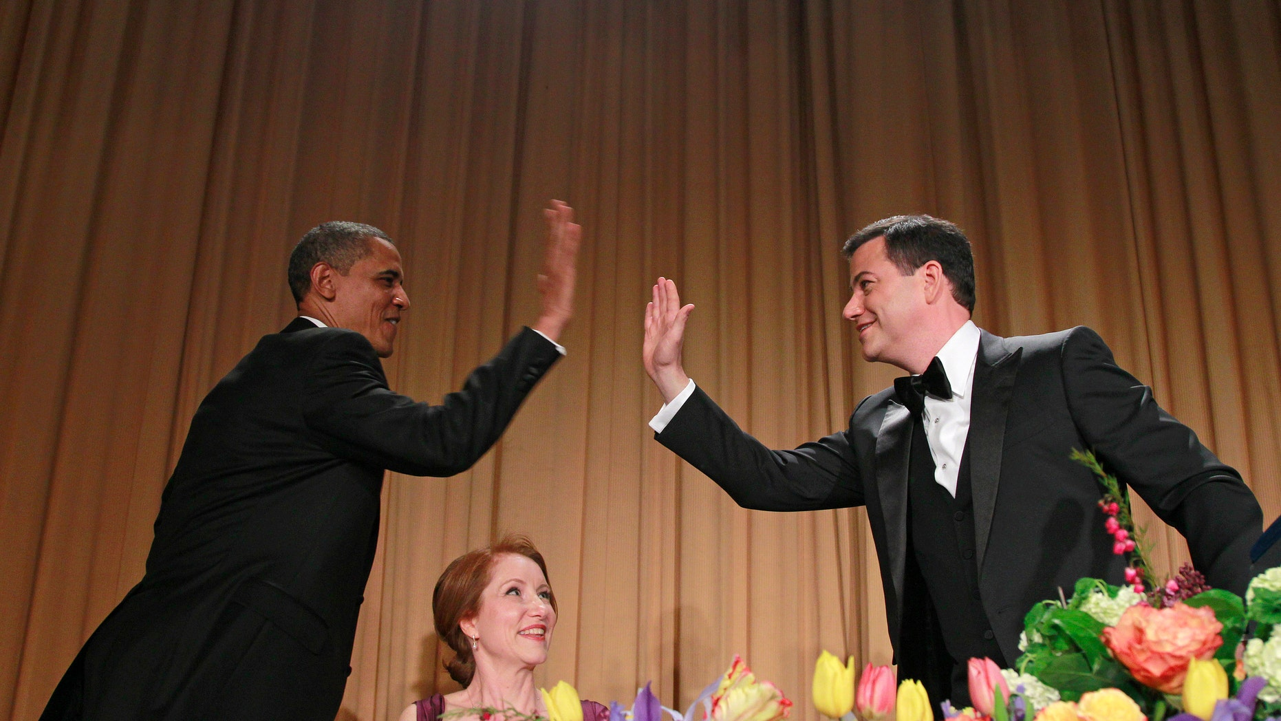 President Barack Obama high-fives late-night comic Jimmy Kimmel as Caren Bohan, a Reuters journalist and president of the White House Correspondents' Association looks on during the White House Correspondents' Association Dinner, Saturday, April 28, 2012 in Washington. (AP Photo/Haraz N. Ghanbari)