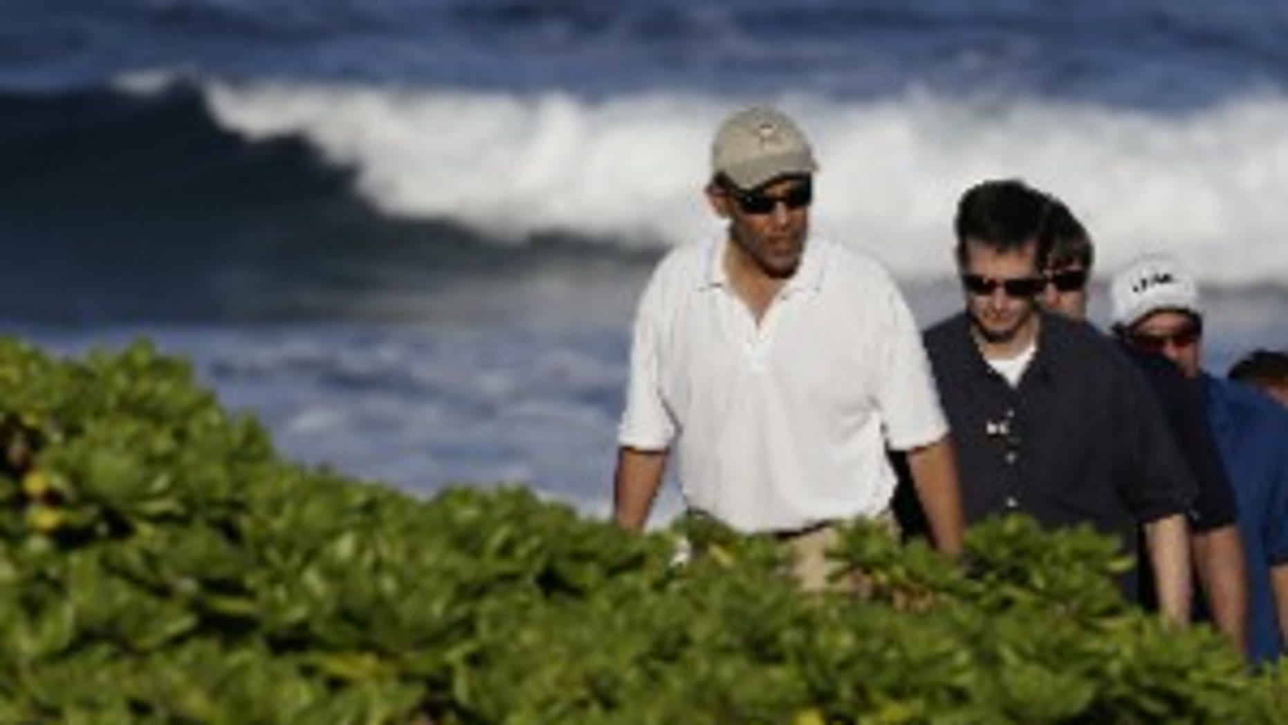 President Barack Obama, left, walks on Pyramid Rock beach on Marine Corps Base Hawaii in Kaneohe Bay, Hawaii Saturday, Dec. 26, 2009. The Obamas are in Hawaii for the holidays.(AP Photo/Alex Brandon)