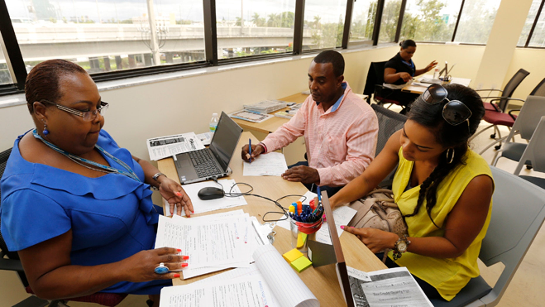 FILE: October 2, 2013: A certified application counselor takes information from two Florida residents about Affordable Care Act insurance, at the Borinquen Medical Center, in Miami, Fla.