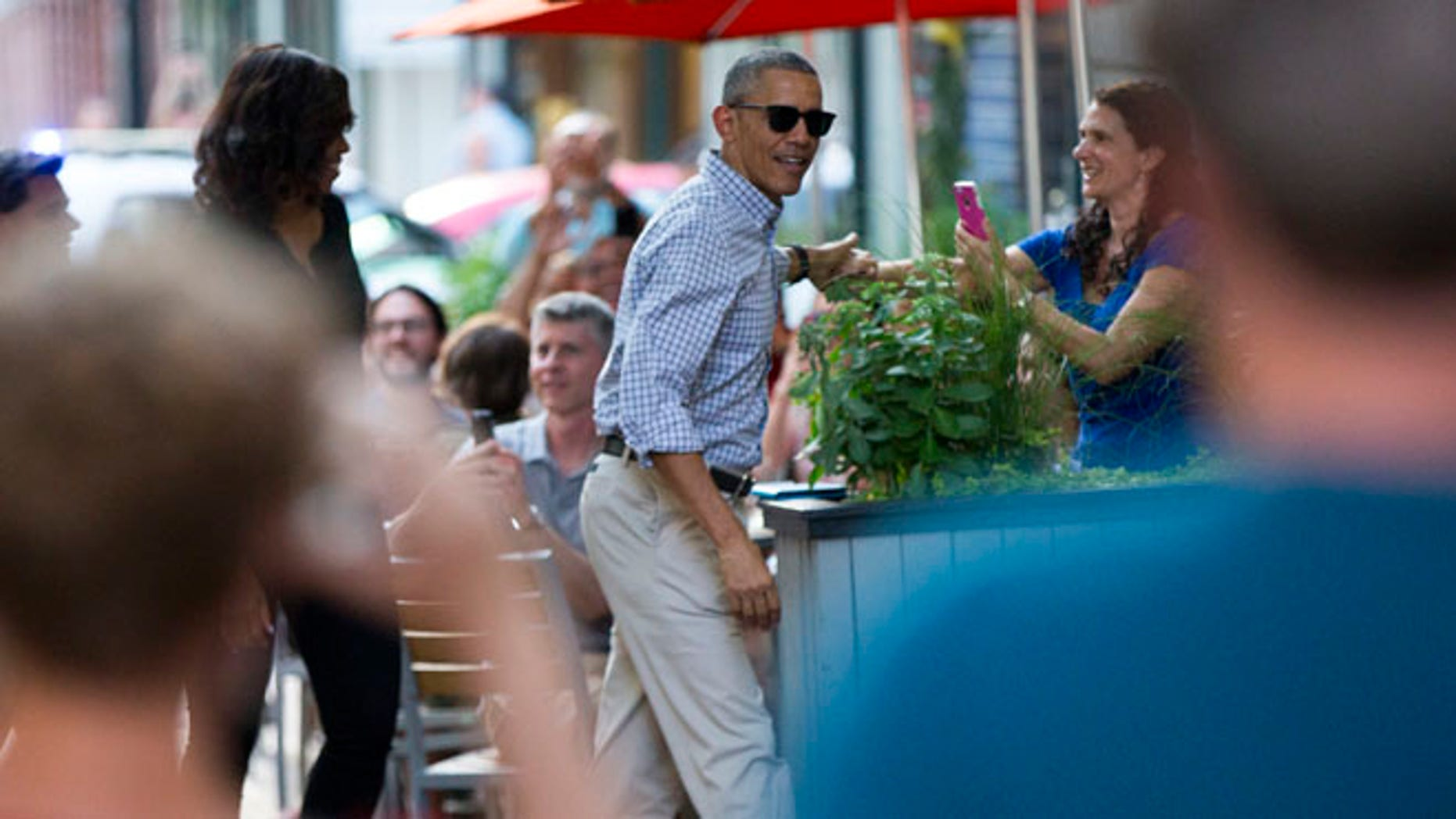 People take photographs as President Barack Obama, center, and first lady Michelle Obama walk into the Oyamel Cocina Mexicana restaurant in Washington for dinner on Saturday, May 28, 2016. (AP Photo/Evan Vucci)