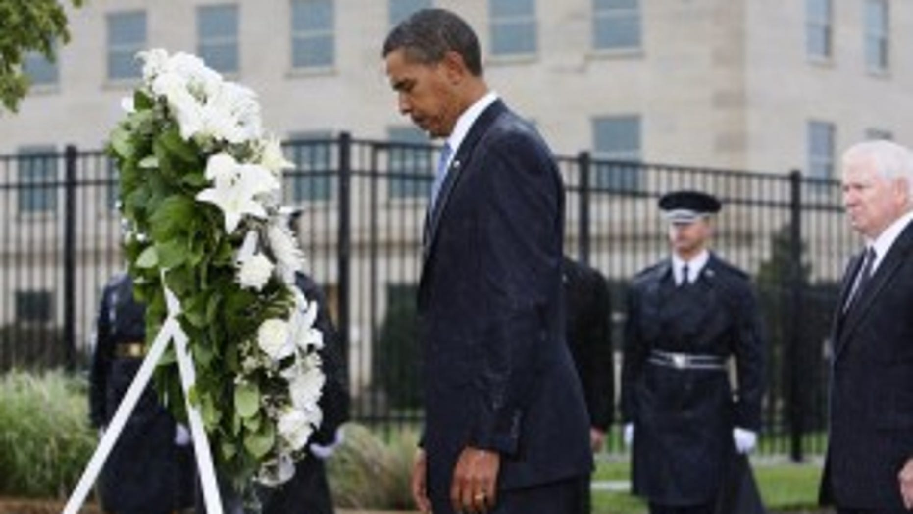 Standing in a steady rain, President Barack Obama bows his head as he lays a wreath at the Pentagon Memorial, marking the eighth anniversary of the Sept. 11 attacks, Friday, Sept. 11, 2009, at the Pentagon. Defense Secretary Robert Gates is at right. (AP Photo/Charles Dharapak)