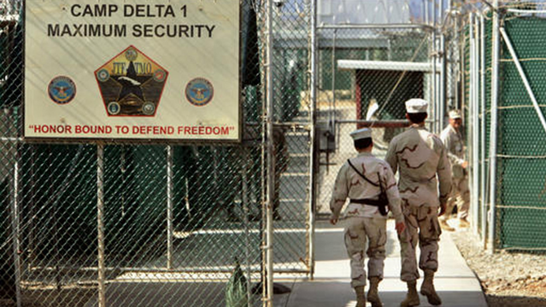 FILE - In this June 27, 2006 file photo, reviewed by a Defense Department, U.S. military guards walk within Camp Delta military-run prison, at the Guantanamo Bay U.S. Naval Base, Cuba. A federal appeals court expressed concerns on Thursday, Sept. 8, 2016, about the prospect of ordering the Obama administration to release graphic videos of a former Guantanamo Bay inmate being force-fed during a hunger strike.  (AP Photo/Brennan Linsley, File)