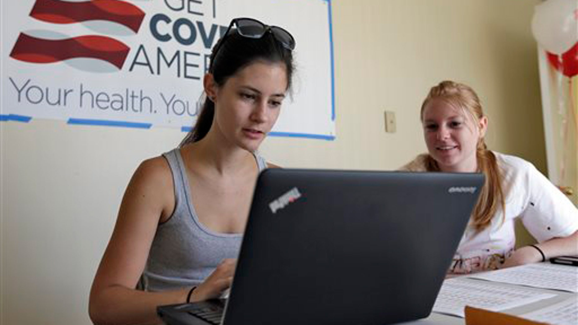 FILE -- Oct. 1, 2013: Ashley Hentze, left, of Lakeland, Fla., gets help signing up for the Affordable Care Act from Kristen Nash, a volunteer with Enroll America, a private, non-profit organization running a grassroots campaign to encourage people to sign up for health care in Tampa, Fla.