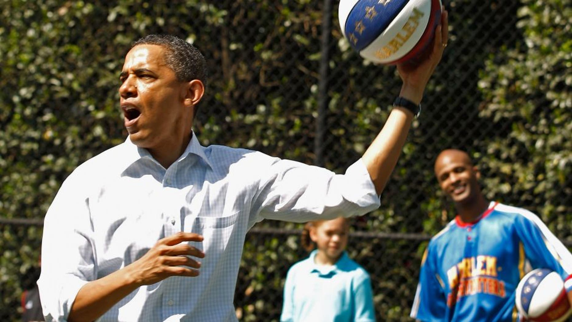 """WASHINGTON, DC - APRIL 25: (AFP OUT) U.S. President Barack Obama shoots a basketball while participating in a """"Let's Move"""" clinic with members of the NBA, WNBA and the Harlem Globetrotters during the White House Easter Egg Roll on the South Lawn of the White House April 25, 2011 in Washington, DC. About 30,000 people are expected to attend the 133-year-old tradition of rolling colored eggs down the White House lawn. (Photo by Chip Somodevilla/Getty Images)"""