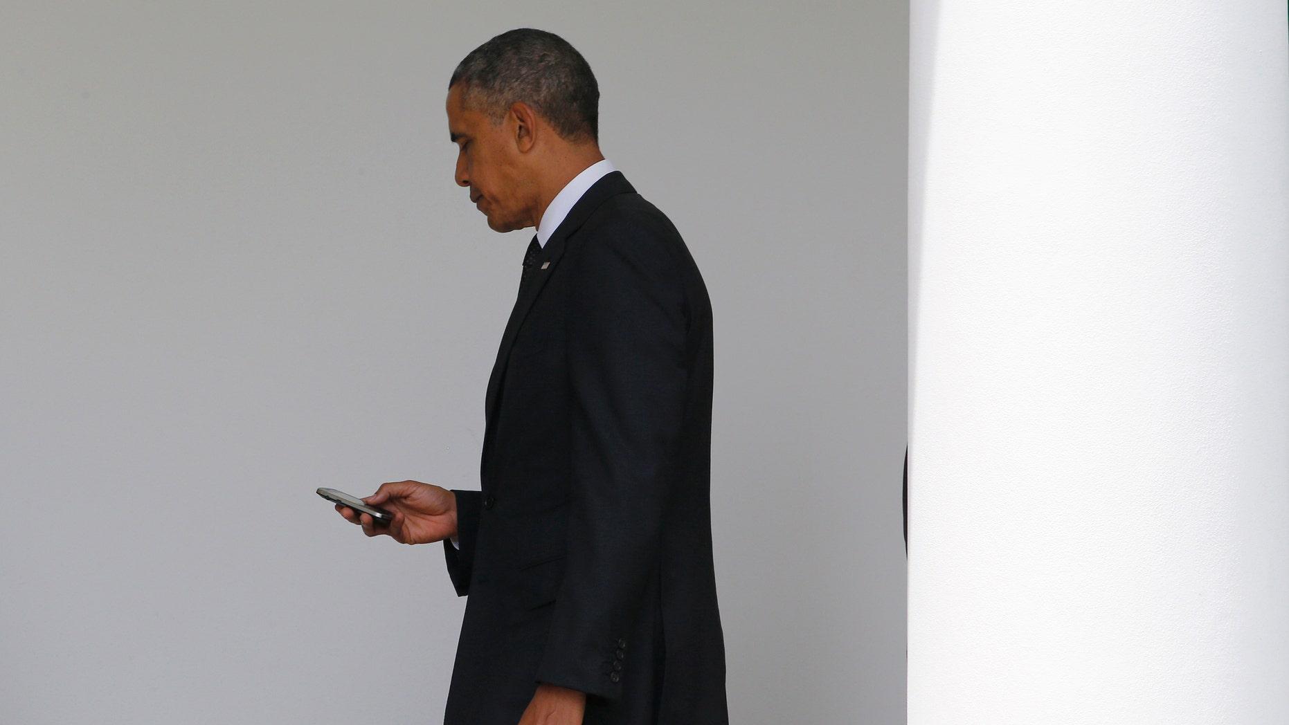 File photo - President Barack Obama checks his Blackberry smartphone.