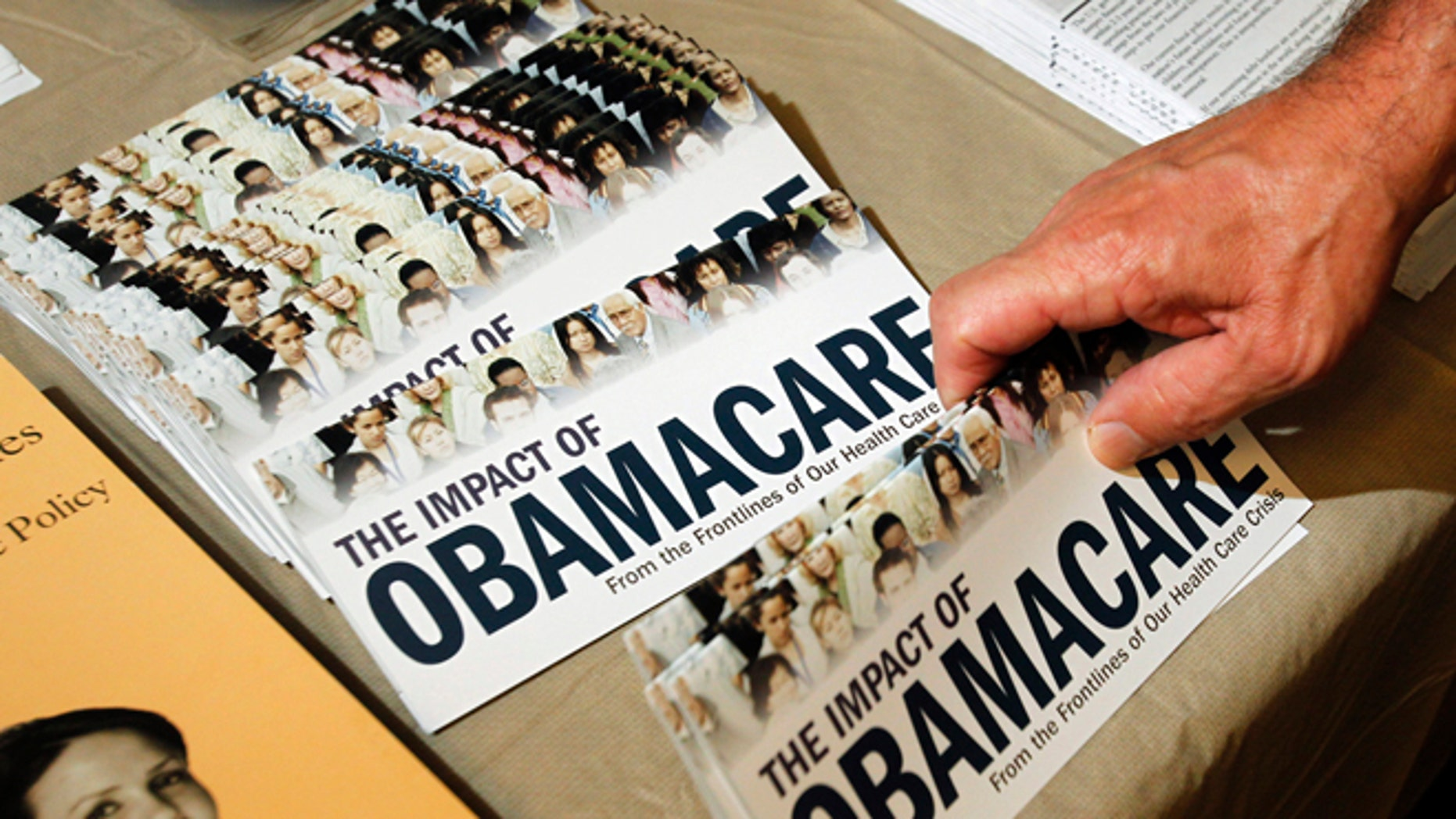 FILE: July 2, 2013: A Tea Party member reaches for a pamphlet on the impact of ObamaCare, at a rally in Littleton, New Hampshire.