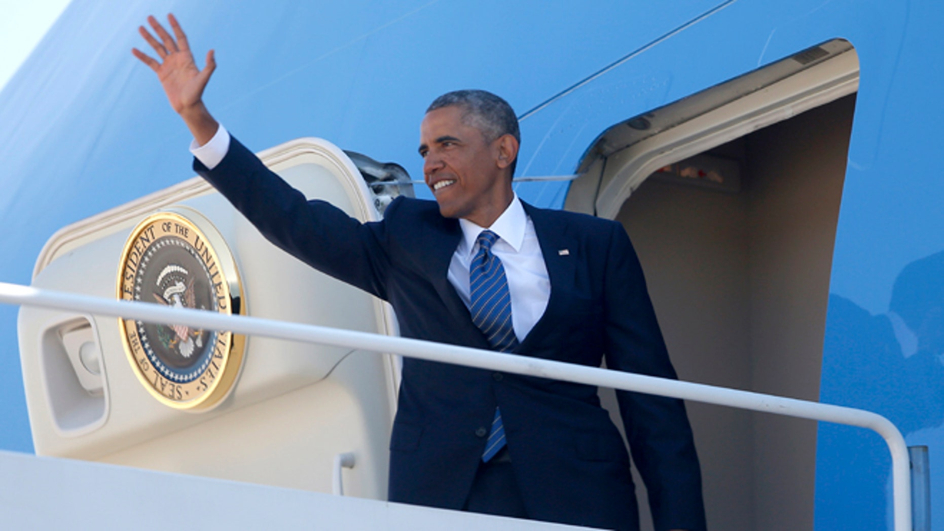 President Obama waves as he boards Air Force One at Andrews Air Force Base, Md., Tuesday, Aug. 26, 2014.