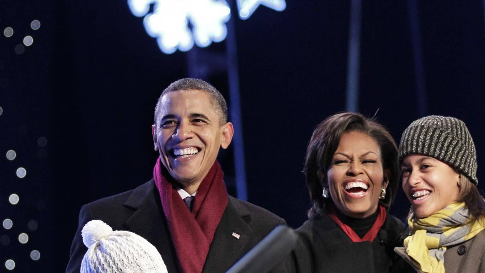 President Barack Obama, with first lady Michelle Obama and daughters Malia, 12, and Sasha, 9, smile as they push the button to light up the National Christmas Tree on the Ellipse, just south of the White House, in Washington, Thursday, Dec. 9, 2010. (AP Photo/J. Scott Applewhite)