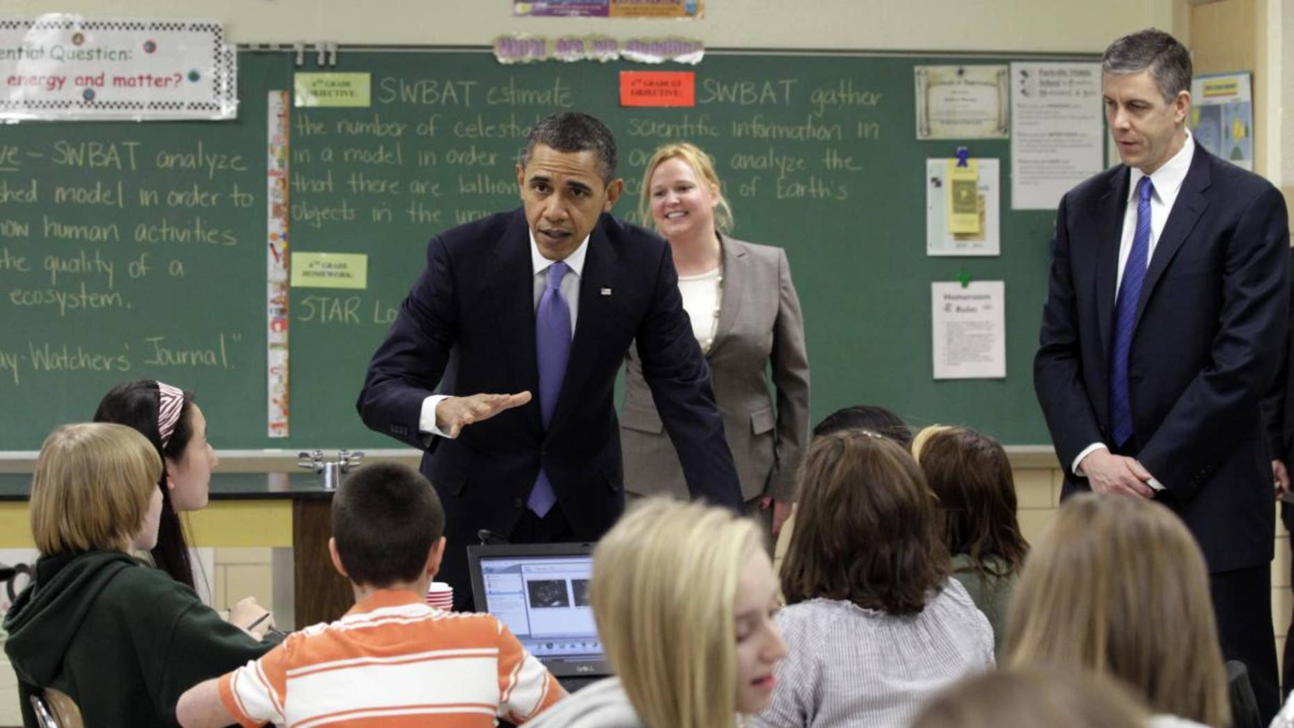President Barack Obama, left, and U.S. Education Secretary Arne Duncan visit Susan Yoder's, center, science class at Parkville Middle School and Center of Technology, in Parkville, Md., Monday, Feb., 14, 2011. (AP Photo/Carolyn Kaster)