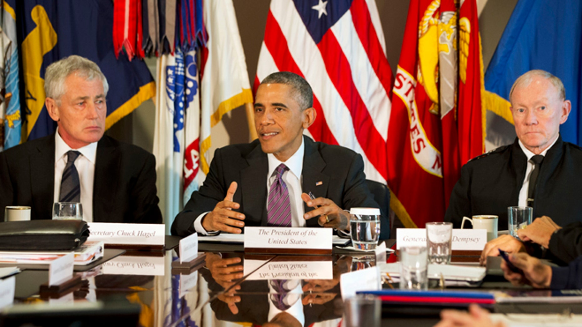 In this Wednesday, Oct. 8, 2014 photo, President Barack Obama, flanked by Defense Secretary Chuck Hagel, left, and Joint Chiefs Chairman Gen. Martin Dempsey, speaks to the media at the conclusion of a meeting with senior military leadership at the Pentagon.