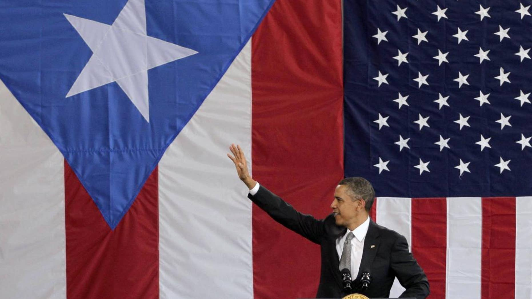 President Barack Obama waves to a crowd gathered inside a hangar at the Muniz Air National Guard Base, shortly after his arrival in San Juan, Puerto Rico, Tuesday, June 14, 2011. Obama's visit to Puerto Rico marks the first by a sitting U.S. President since John Kennedy. Obama is backed by Puerto Rican and American flags. (AP Photo/Brennan Linsley)